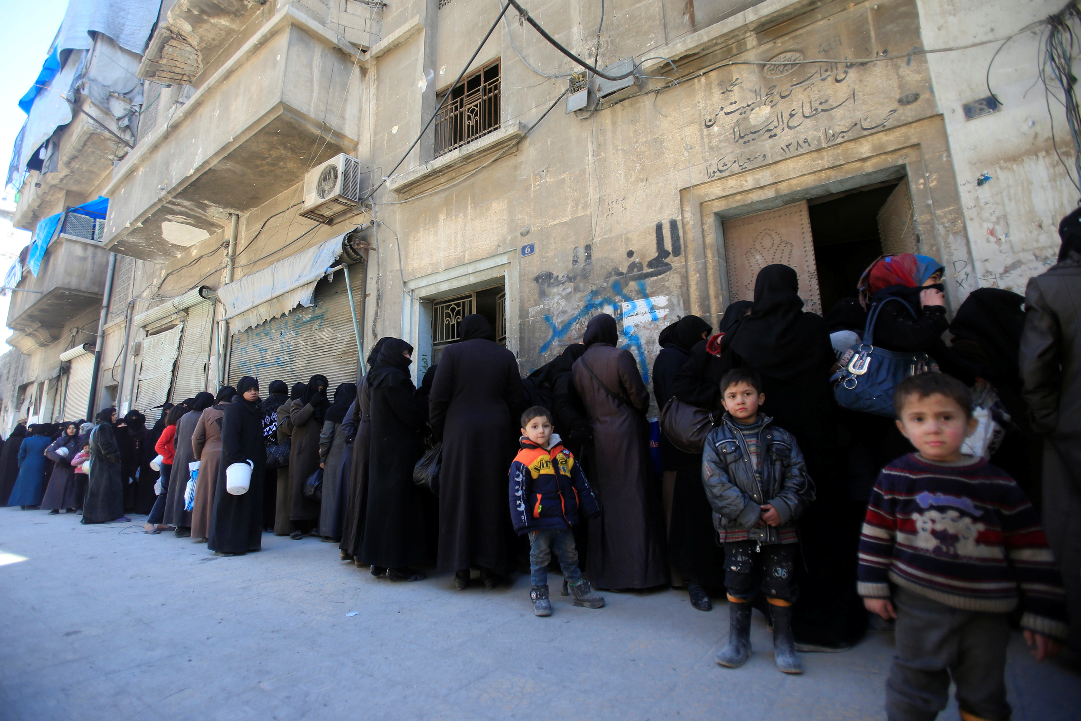 Women and children queue to receive free meals in Aleppo, Syria February 2, 2017. REUTERS/Ali Hashisho - RTX2ZEBF