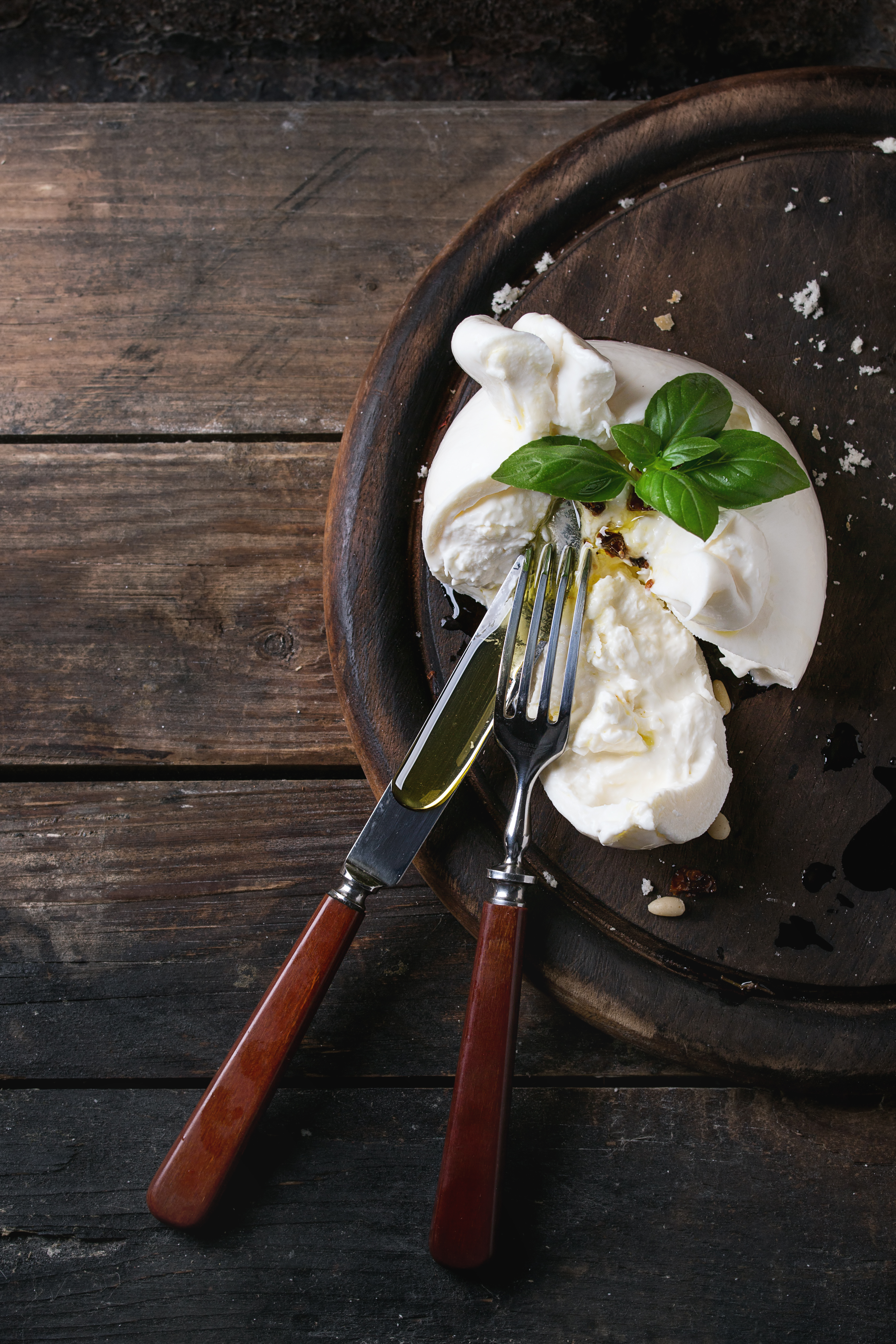 Sliced Italian cheese burrata served on round chopping board with pine nuts, basil and dried tomatoes in olive oil with fork and knife over old wood background. Overhead view