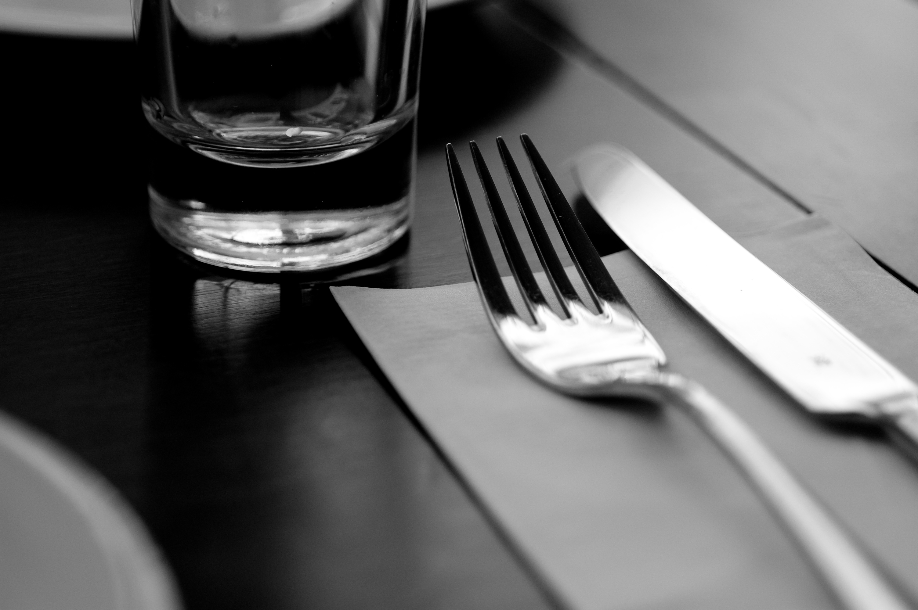 Table setting of fork, knife, napkin, glass and plate at cafe.