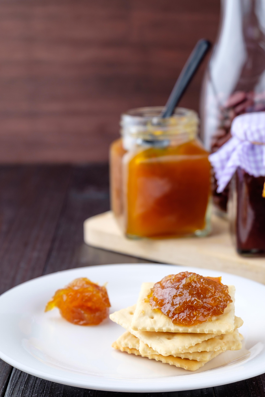 Crackers with orange jam on wooden background