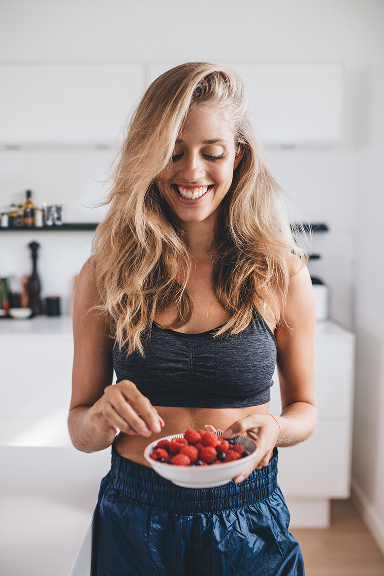 Healthy young woman in kitchen holding a bowl of berries. Smiling woman having healthy breakfast at home.