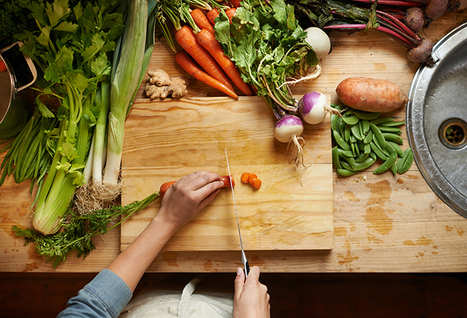 High angle shot of a woman cutting up vegetables on a cutting board