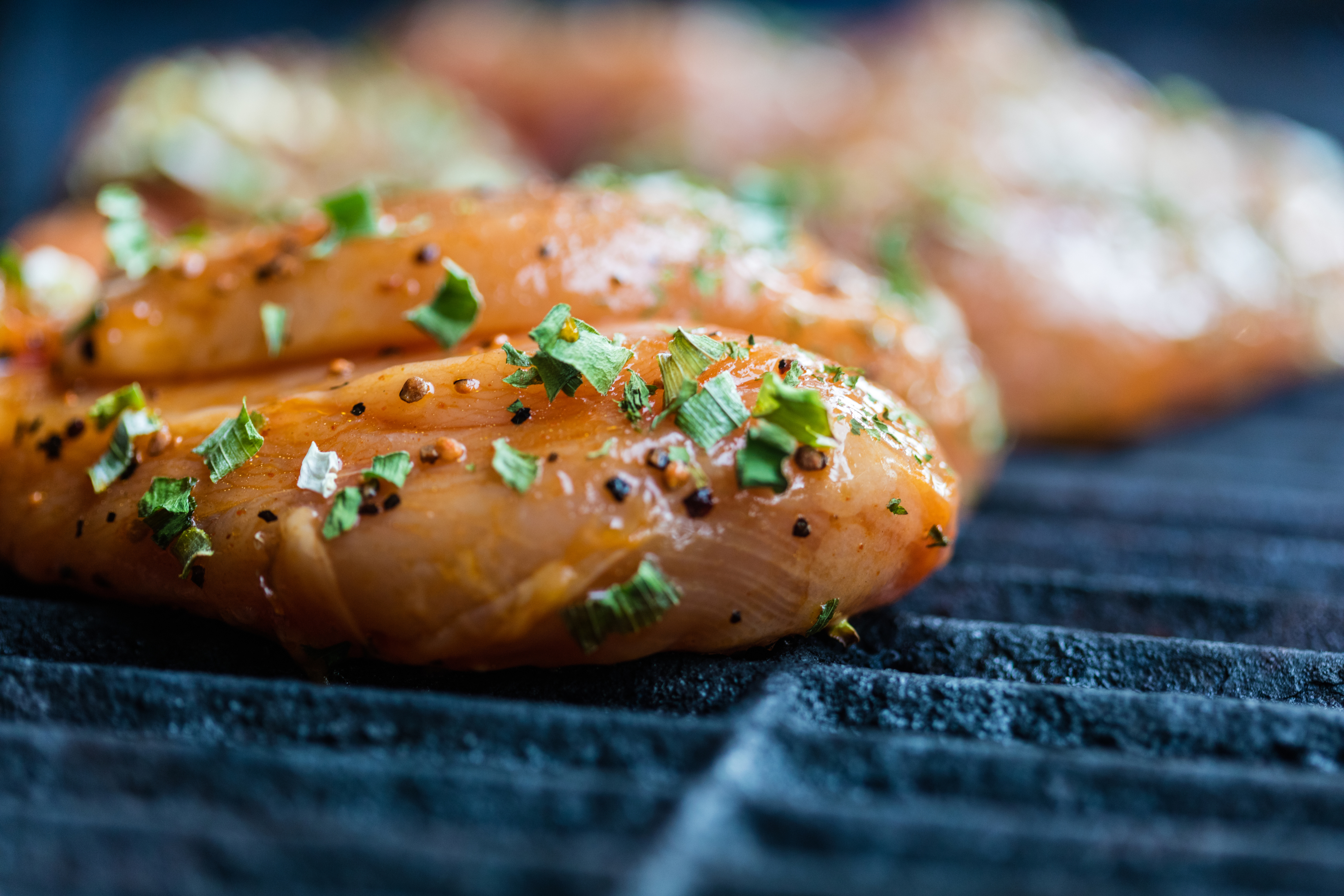 Raw marinated chicken breasts cooking on the BBQ grill.