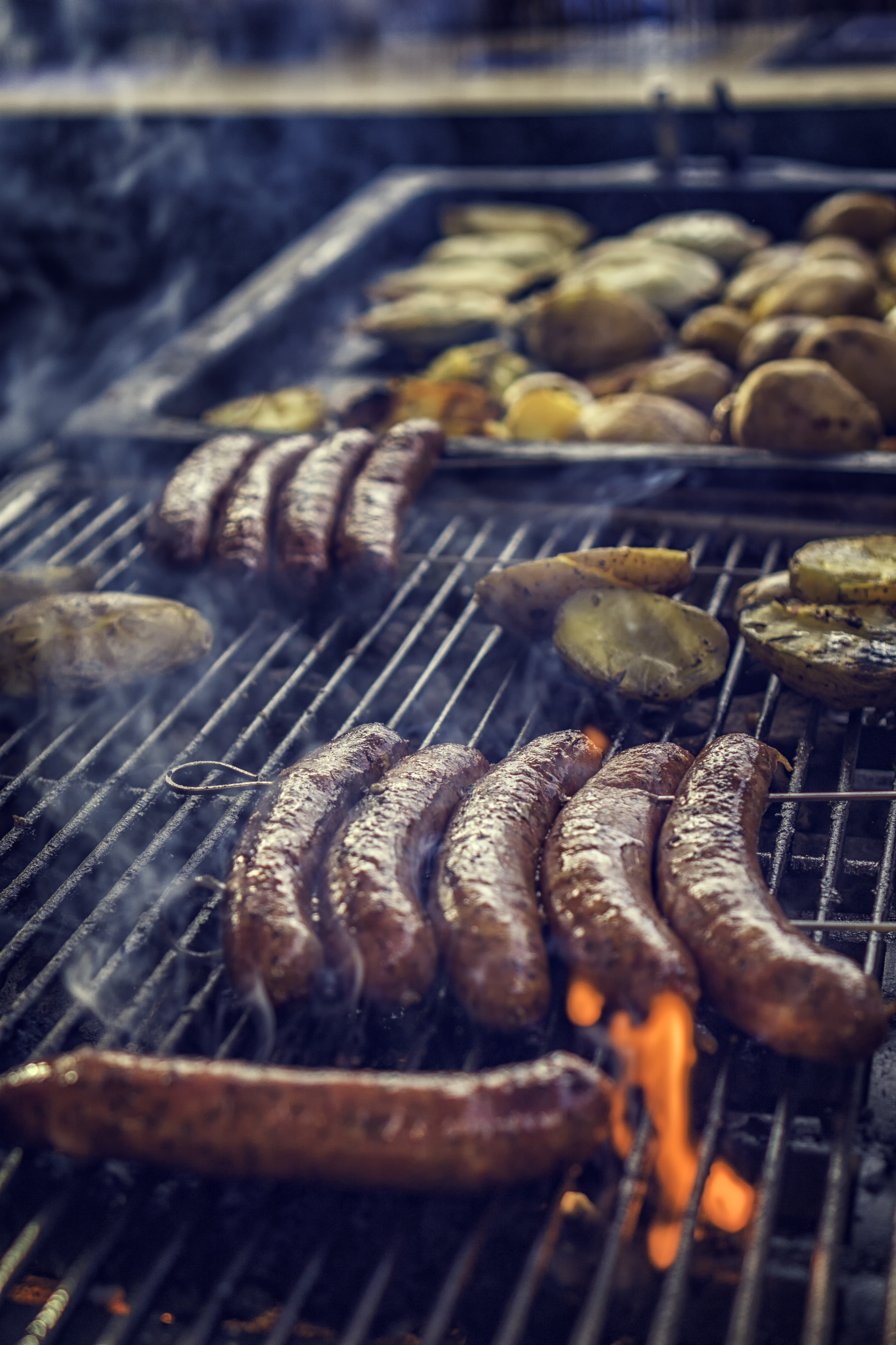 Delicious street food with grilled chorizo and potatoes on a barbecue grill