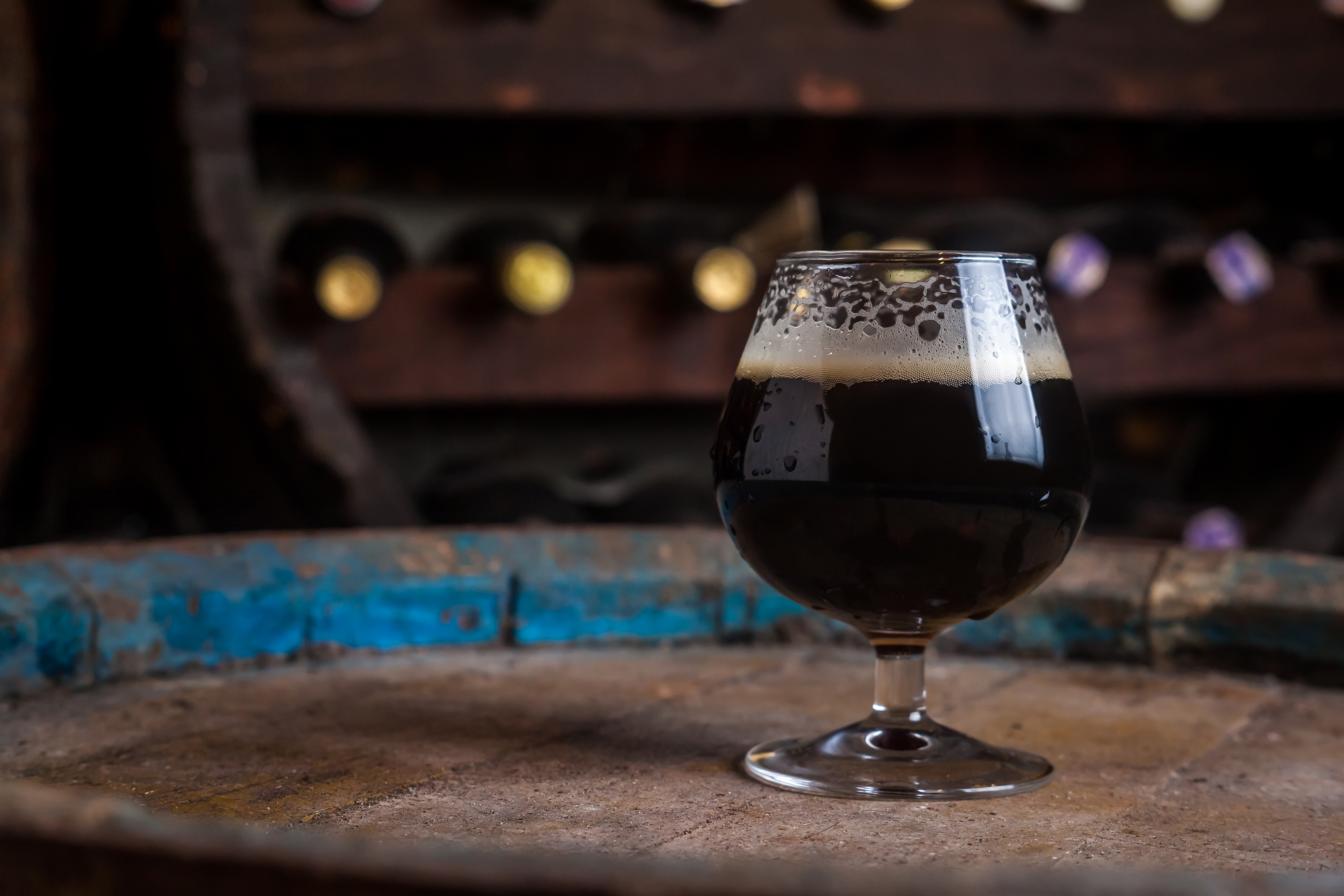 Snifter glass full of dark ale standing on a wooden barrel in a cellar