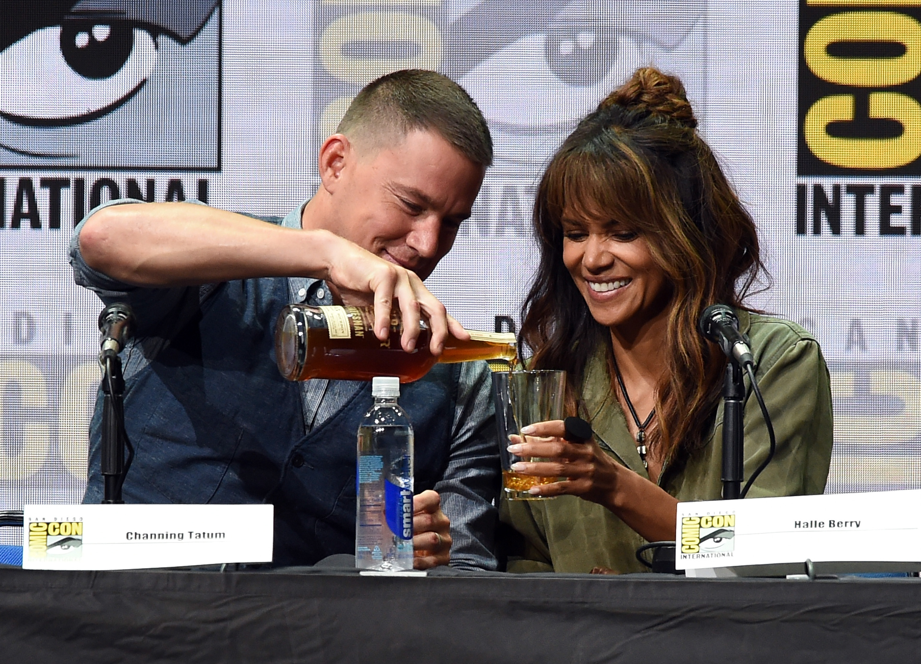 SAN DIEGO, CA - JULY 20:  Actor Channing Tatum (L) pours actor Halle Berry a drink onstage at the 20th Century FOX panel during Comic-Con International 2017 at San Diego Convention Center on July 20, 2017 in San Diego, California.  (Photo by Kevin Winter/Getty Images)