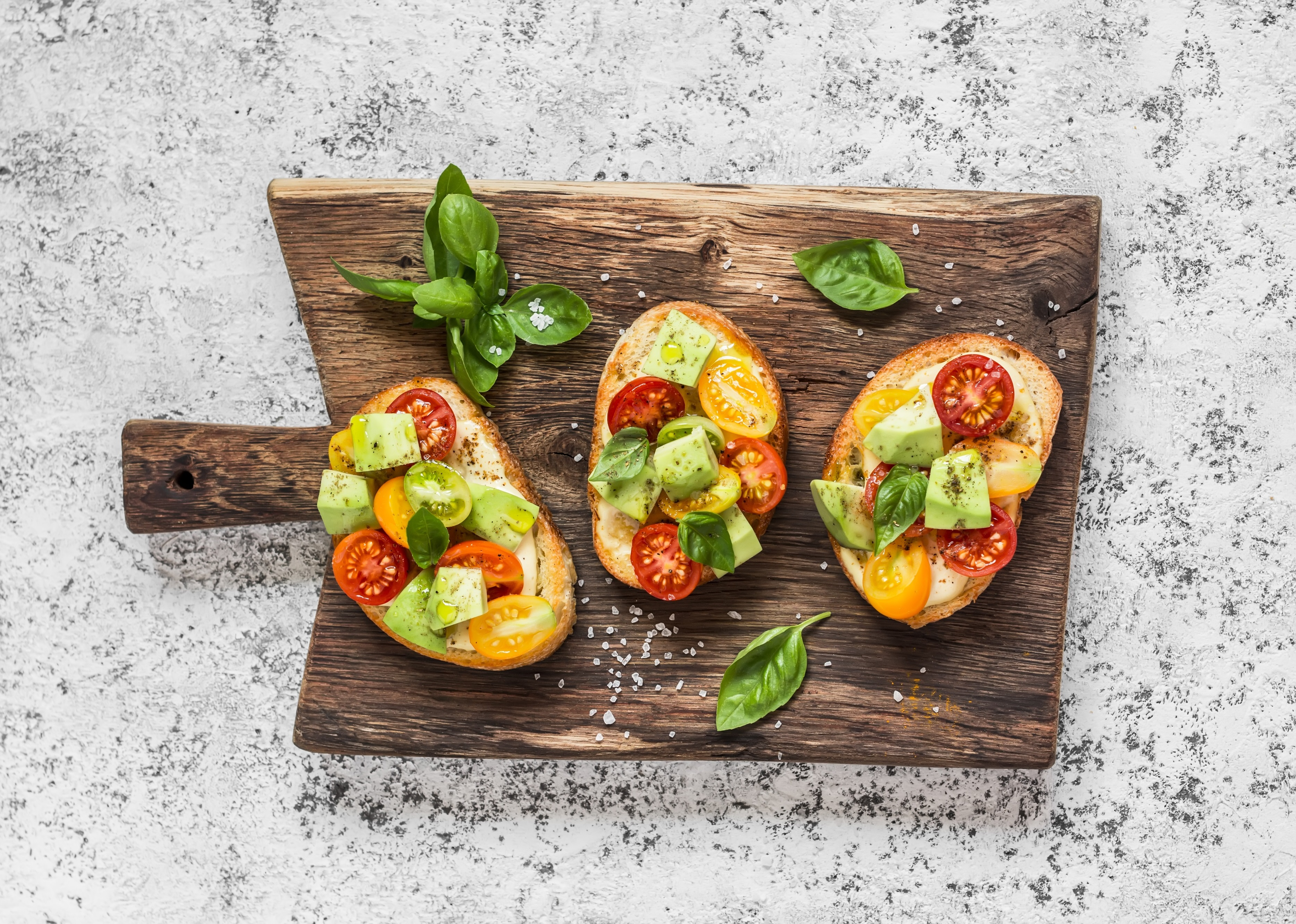 Bruschetta with tomatoes and avocado on rustic wooden cutting board. Delicious snack or appetizer to wine
