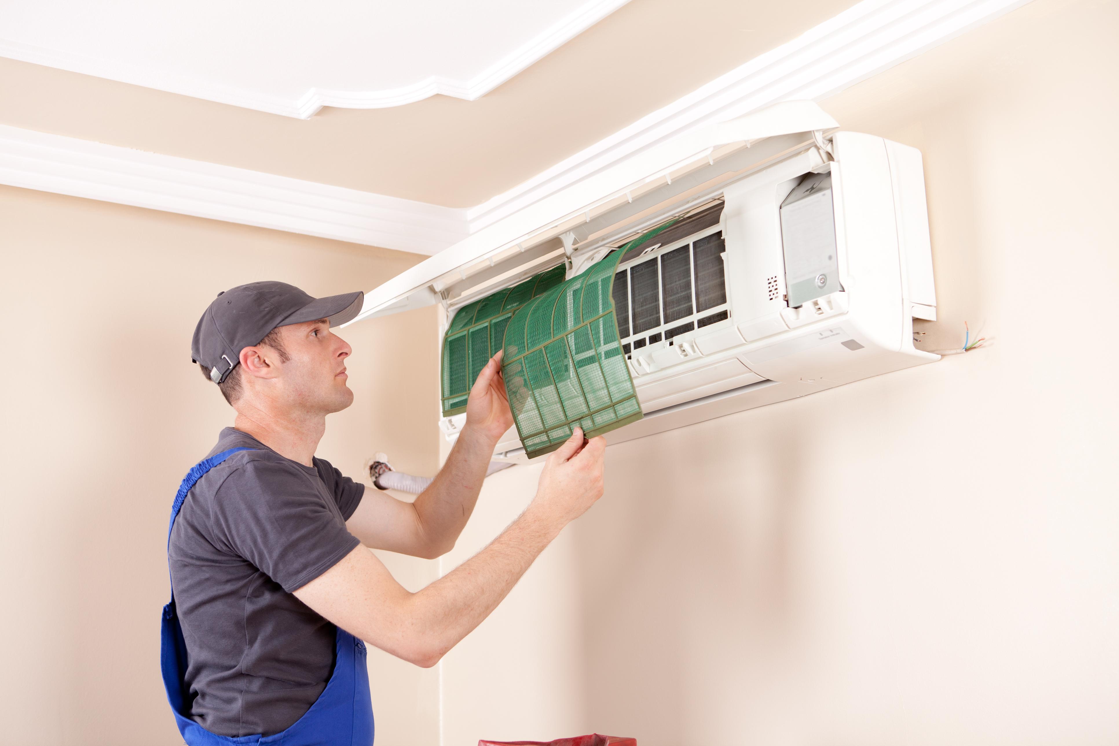 Air conditioner technician servicing indoor.