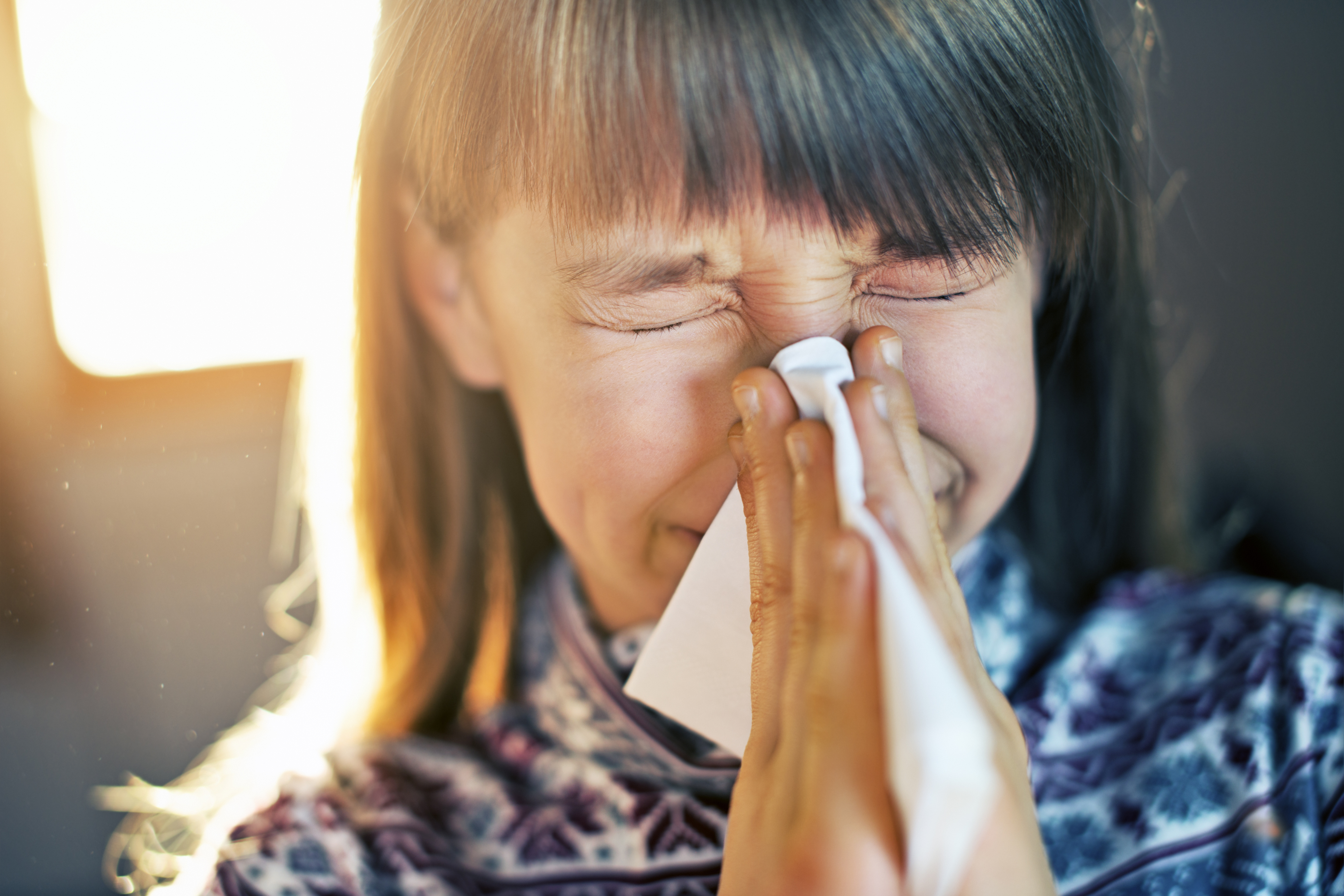 Little girl in dusty home cleaning nose. Dust particles visible in sun rays. The girl aged 9 cleaning her runny nose with a tissue.