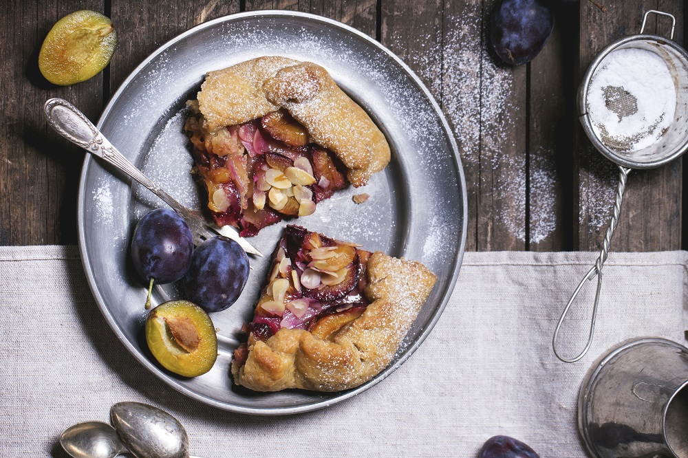 Two pieces of cake galette with plums, served in vintage metal plate over old wooden table. Top view. See series
