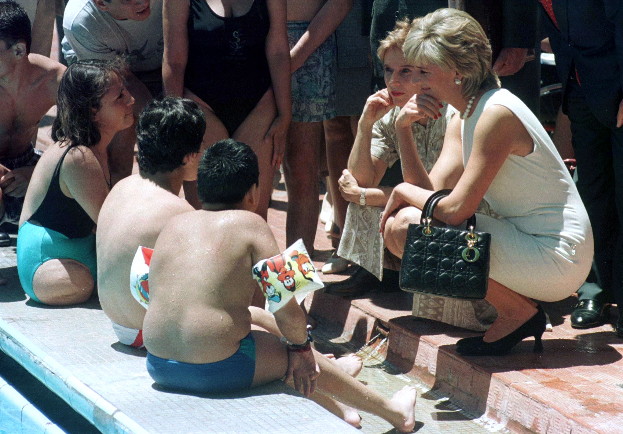 Princess Diana chats with handicapped children beside the pool of the Argentine National Rehabilitation Centre November 23.  The Princess of Wales is on a four-day tour of Argentina - RTXFKST