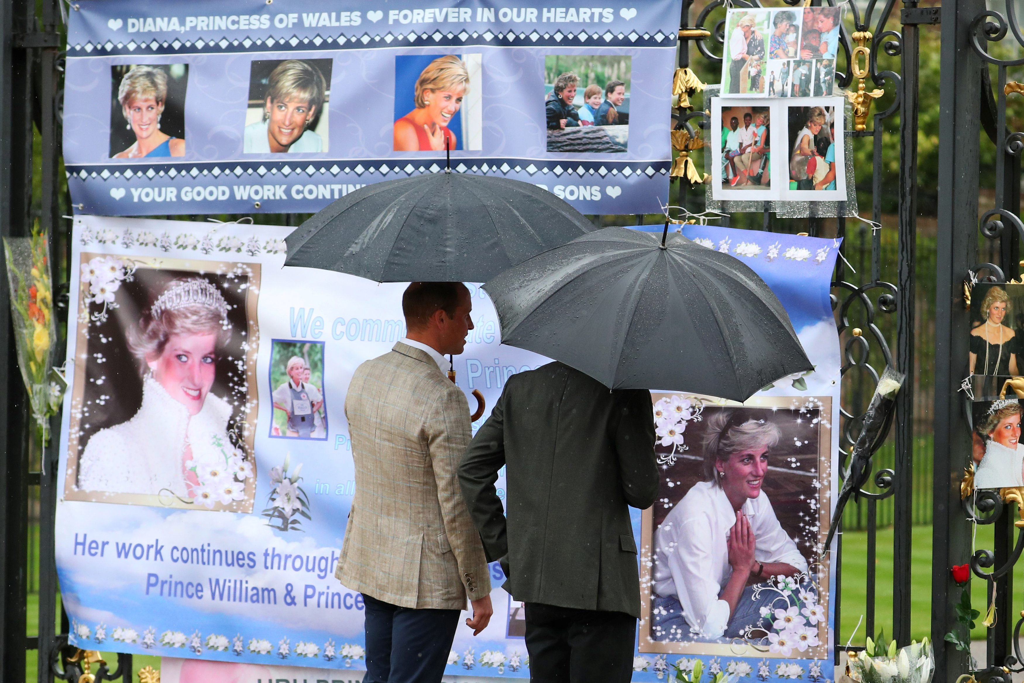 Britain's Prince William, Duke of Cambridge and Prince Harry look at flowers and tributes left in memory of the late Princess Diana at the gates of her former residence Kensington Palace in London, Britain, August 30, 2017. REUTERS/Hannah McKay  NO RESALES. NO ARCHIVES
