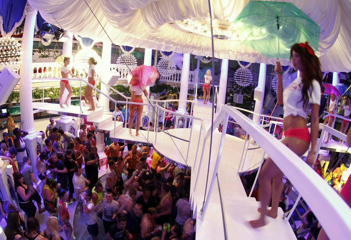 Dancers perform over the crowd during a water party inside Paradis disco in San Antonio in the Spanish Balearic island of Ibiza early June 2, 2012. The island of Ibiza is one the top locations chosen by British citizens to spend their holidays. REUTERS/Enrique Calvo (SPAIN - Tags: TRAVEL SOCIETY) - GM1E86303EA01