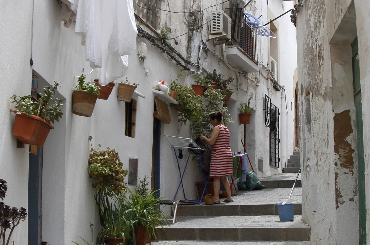 A woman hangs clothes to dry on a central street in Ibiza in the Spanish Balearic island of Ibiza May 29, 2011. REUTERS/Enrique Calvo (SPAIN - Tags: SOCIETY TRAVEL) - GM1E75U0CQV01