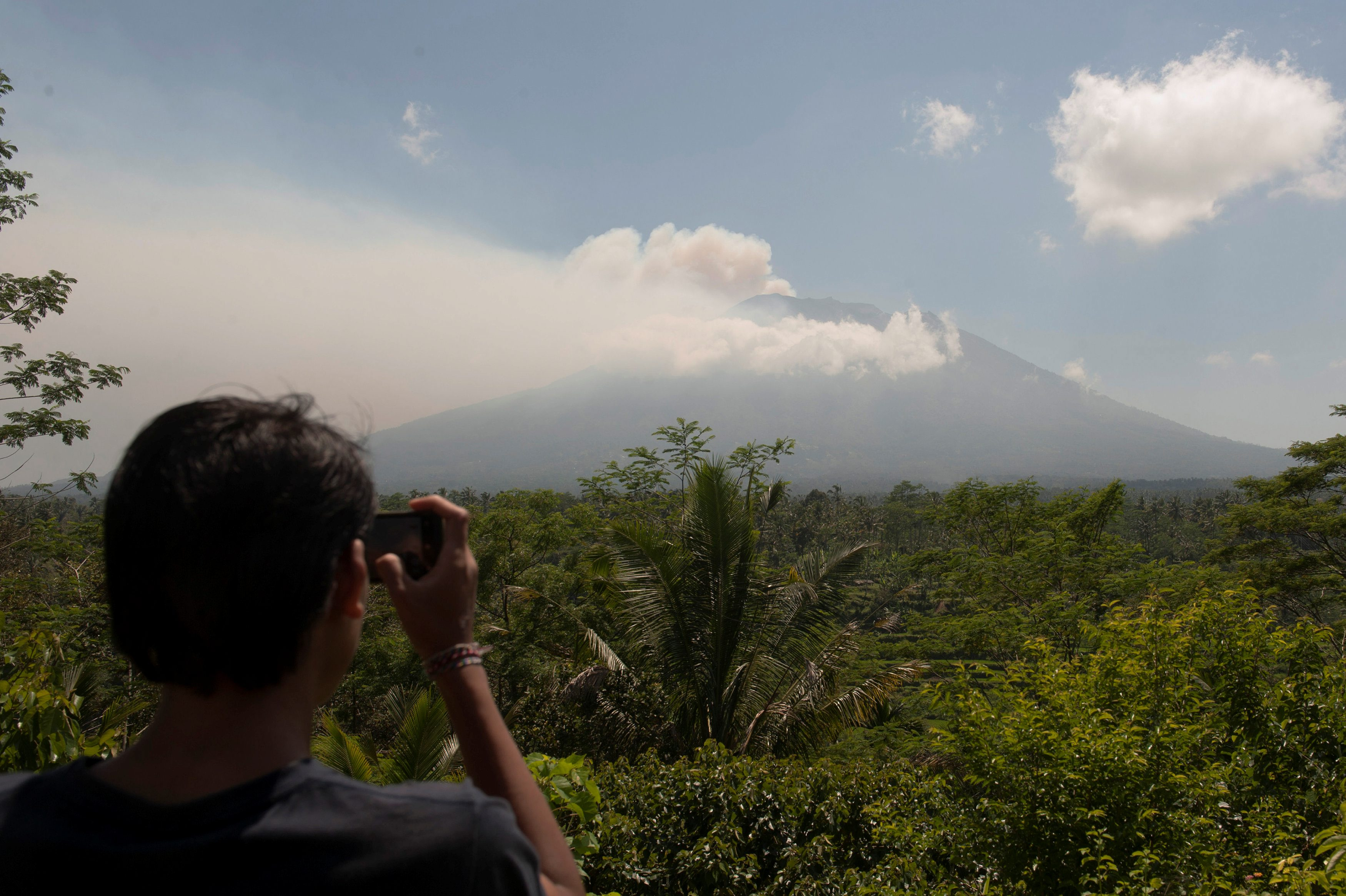 A local resident takes a picture of Mount Agung, an active volcano that authorities say is showing increased activity, from a monitoring station in Rendang Village, Karangasem on the resort island of Bali, Indonesia September 19, 2017 in this photo taken by Antara Foto. Antara Foto/Nyoman Budhiana via REUTERS ATTENTION EDITORS - THIS IMAGE WAS PROVIDED BY A THIRD PARTY. MANDATORY CREDIT. INDONESIA OUT. NO COMMERCIAL OR EDITORIAL SALES IN INDONESIA