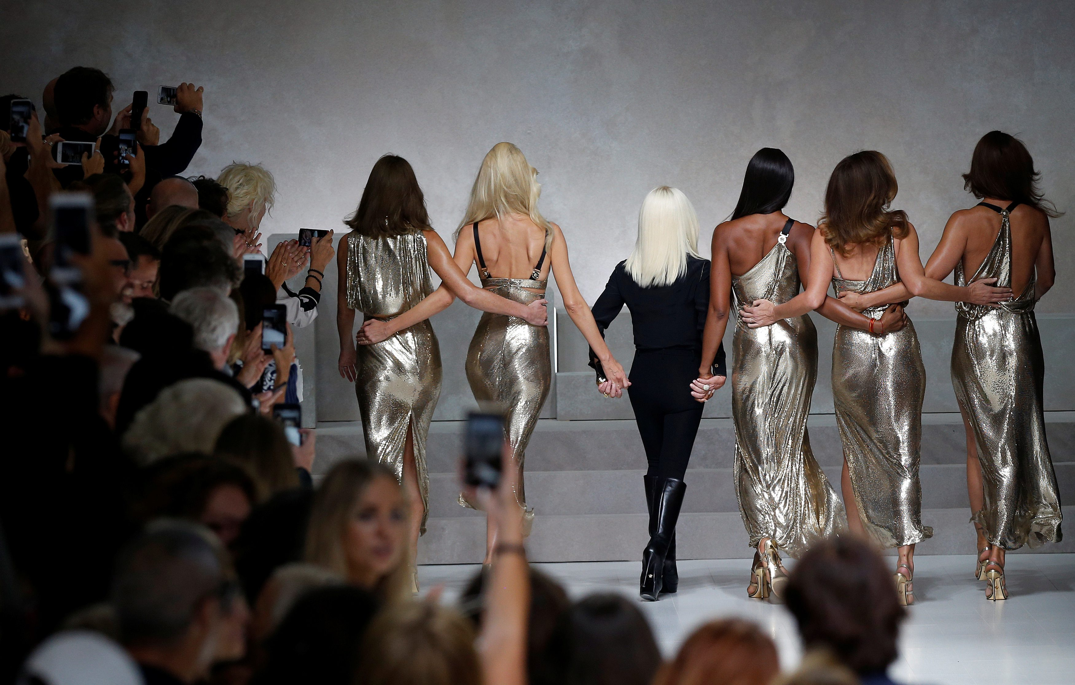 Italian designer Donatella Versace (3L) acknowledges the applause with former top models Carla Bruni (L), Claudia Schiffer, Naomi Campbell, Cindy Crawford and Helena Christensen (R) at the end of Versace Spring/Summer 2018 show at the Milan Fashion Week in Milan, Italy, September 22, 2017. REUTERS/Stefano Rellandini