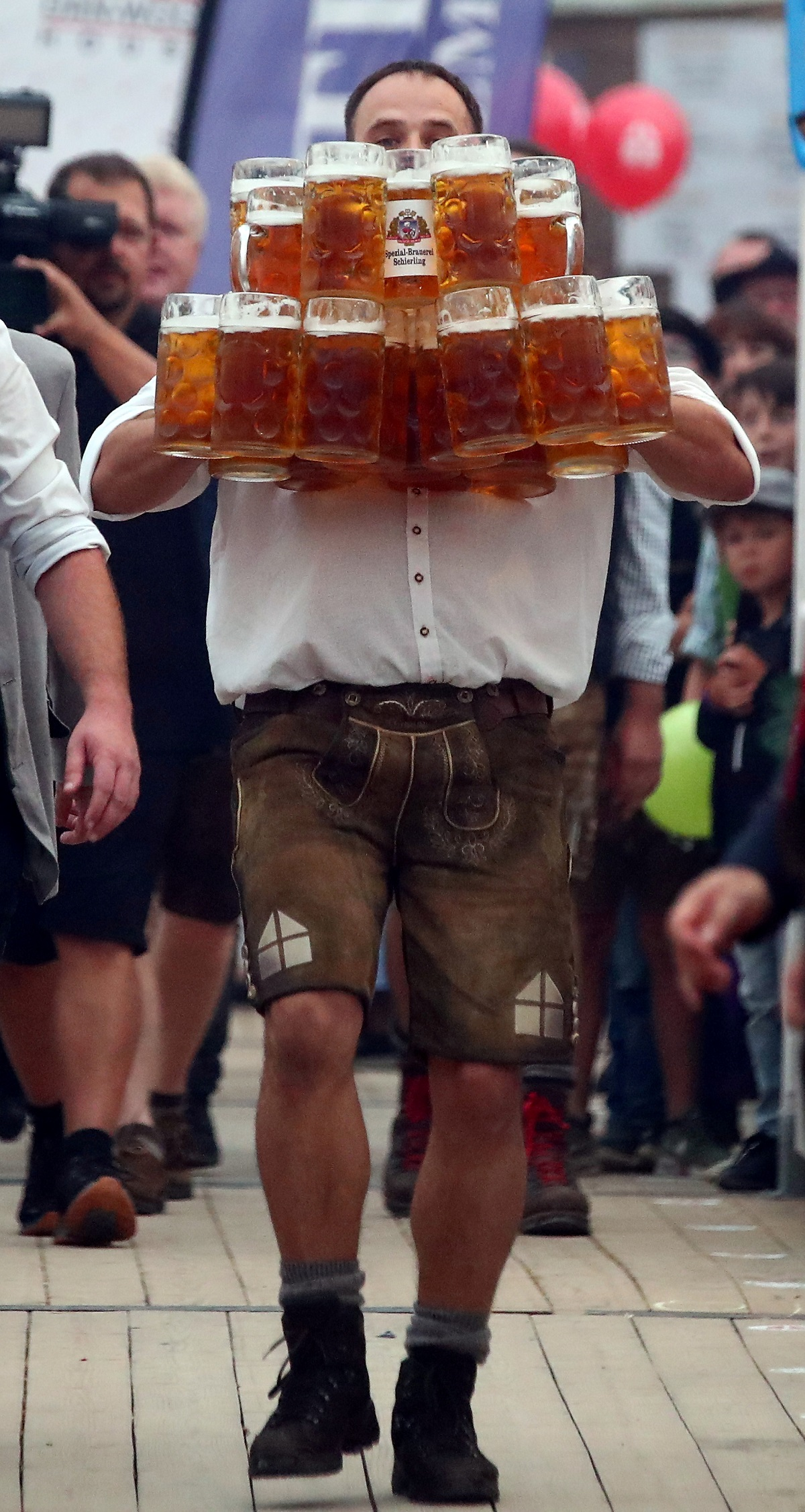 German Oliver Struempfel competes to set a new world record in carrying one liter beer mugs over a distance of 40 m (131 ft 3 in) in Abensberg, Germany September 3, 2017. Struempfel carried 27 mugs over 40 meters to set a new world record. REUTERS/Michael Dalder - RC1D45409C50