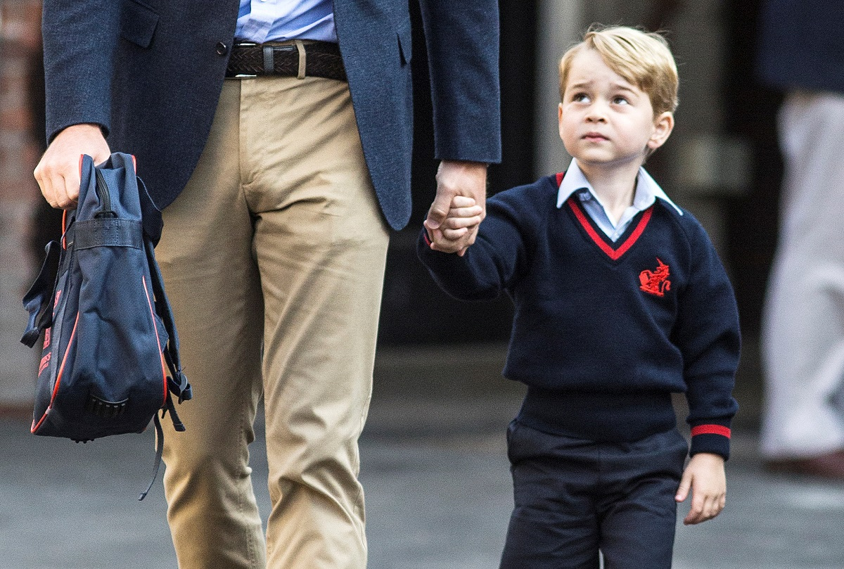 Prince George holds his father Britain's Prince William's hand as he arrives on his first day of school at Thomas's school in Battersea, London, September 7, 2017. REUTERS/Richard Pohle/Pool - RC198E2A37D0