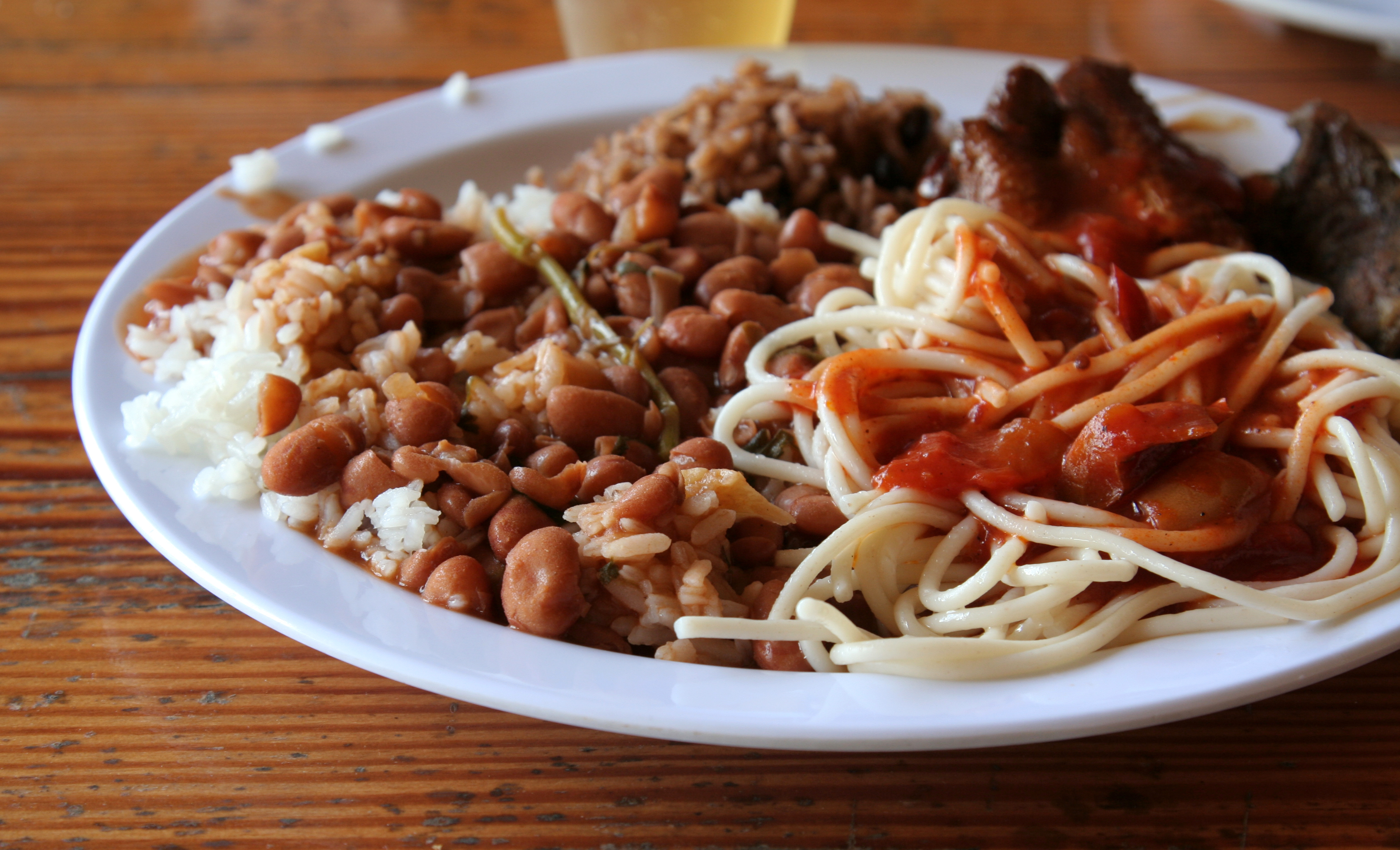 A lunch from the Dominican Republic featuring, beans, rice,spaghetti,chicken and beer. (cervasa)
