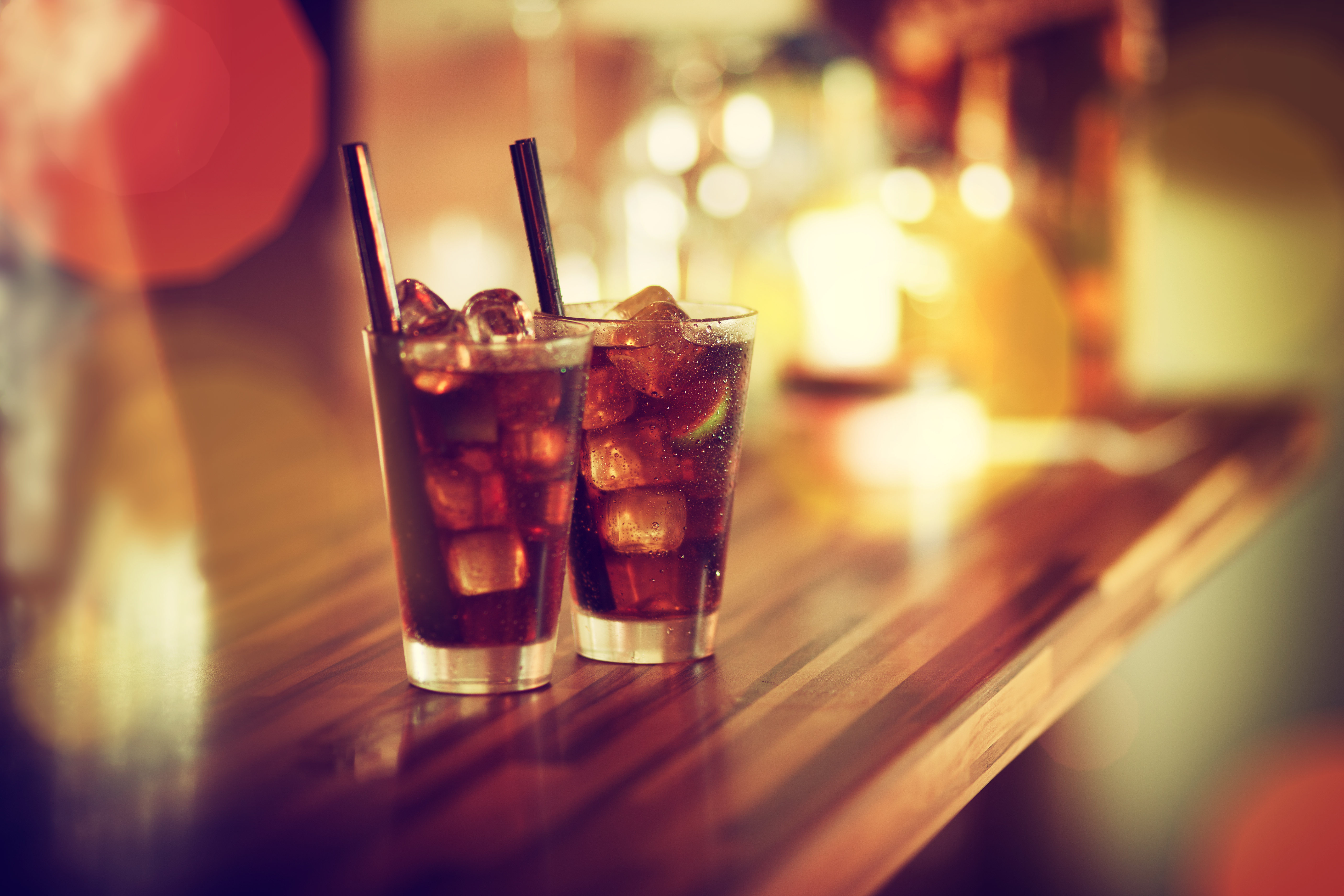 Two glasses of rum-cola cocktail with ice served on the bar. Vintage colour look.