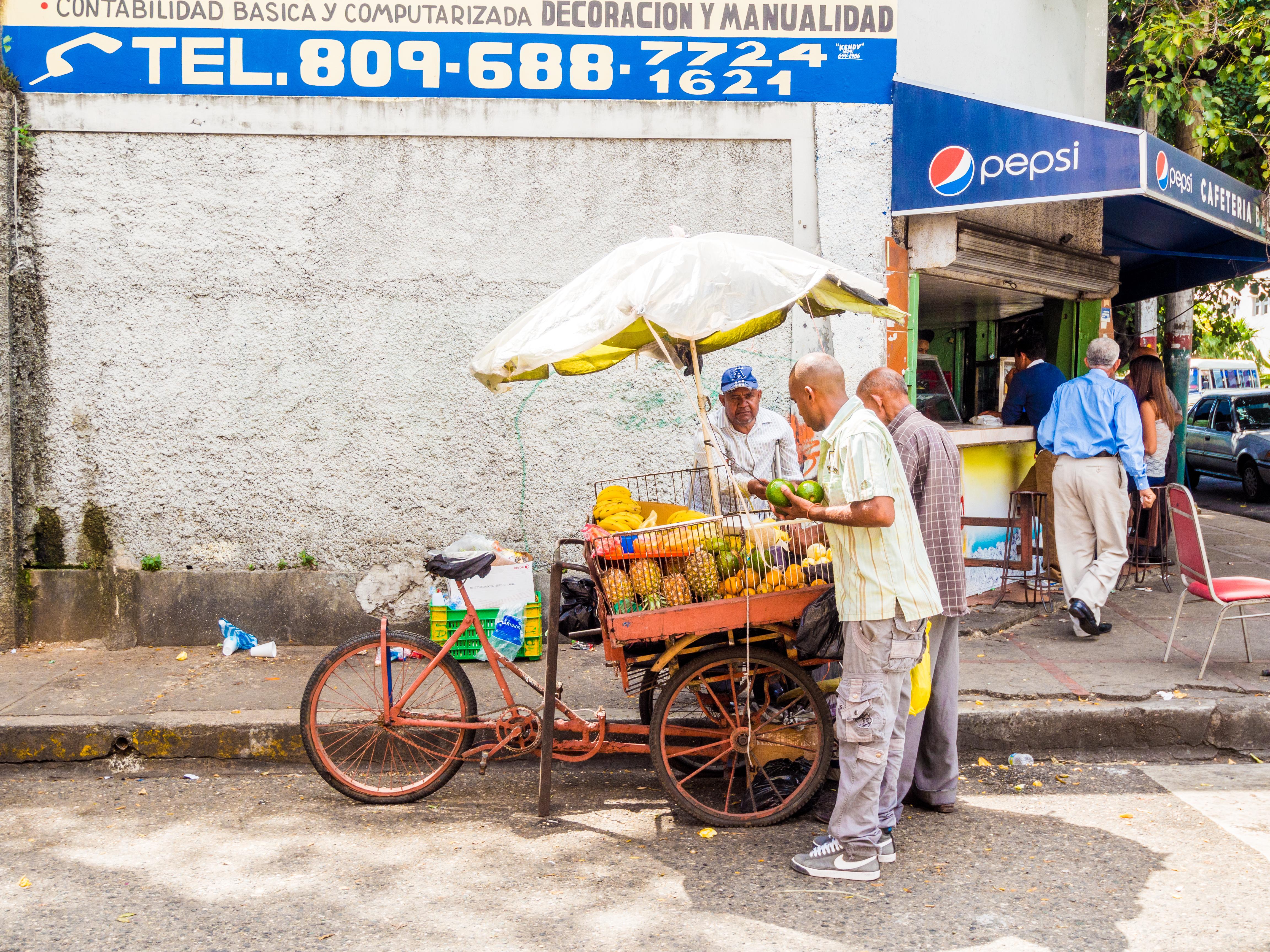 Santo Domingo, Dominican Republic - February 23, 2013: Fruit vendor preparing fruits for his customer in Santo Domingo, Dominican Republic