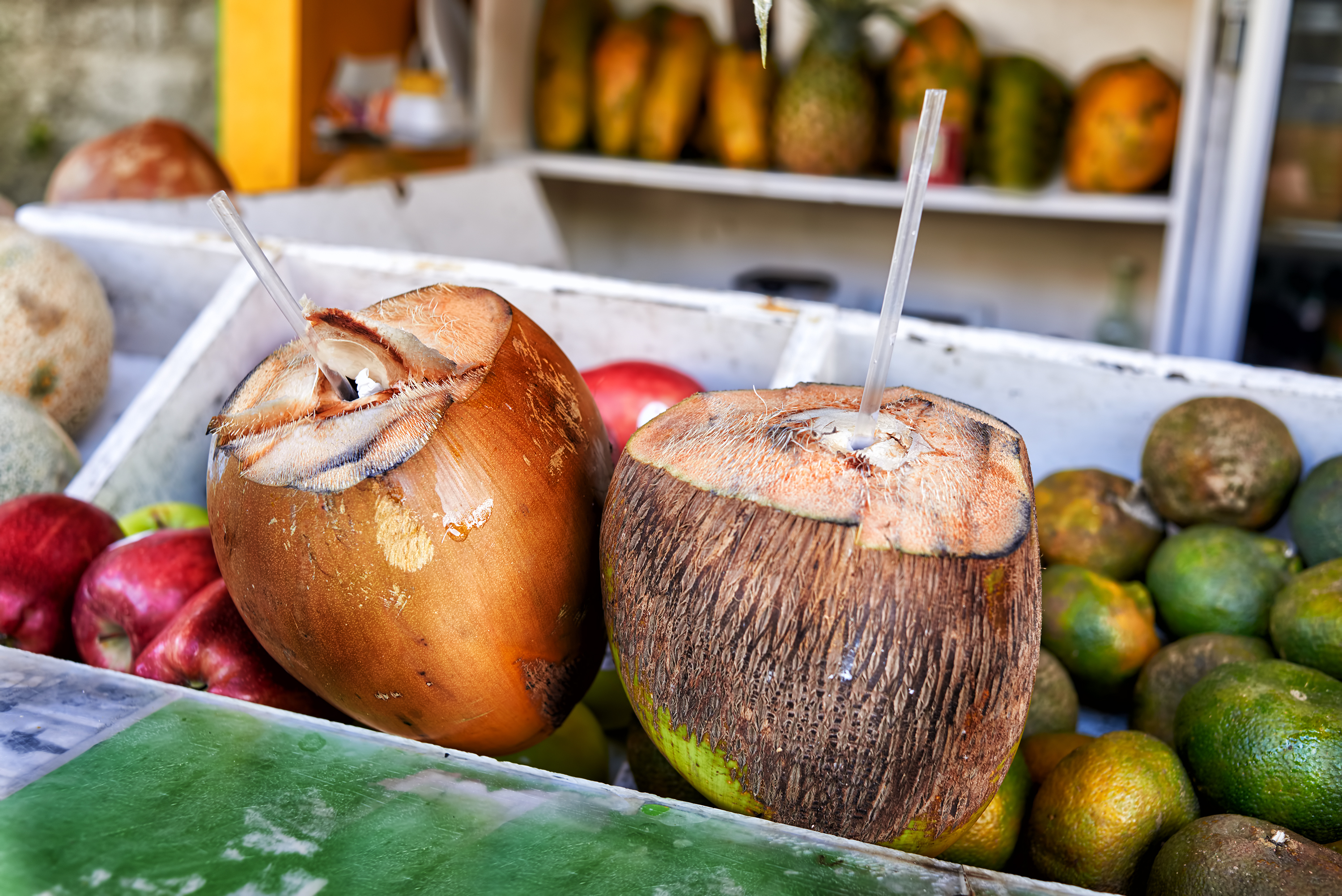 Green coconuts with drinking straws on fruit stand. Coconut water drinks