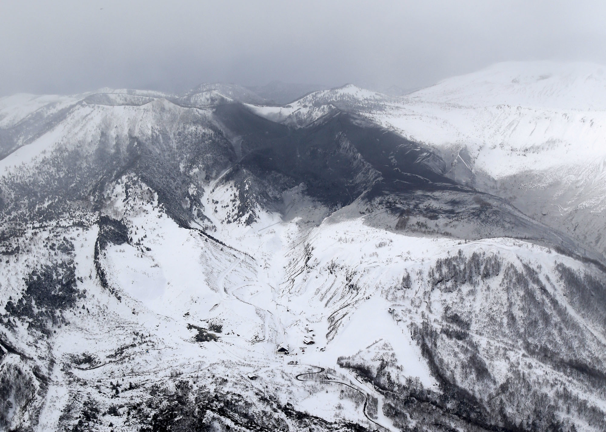 Photo taken from a Kyodo News helicopter on January 23, 2018, shows the area surrounding Mt. Kusatsushirane (top, L) in Gunma Prefecture, northwest of Tokyo, which erupted on the same day.   Mandatory credit Kyodo/via REUTERS ATTENTION EDITORS - THIS IMAGE WAS PROVIDED BY A THIRD PARTY. EDITORIAL USE ONLY. MANDATORY CREDIT. JAPAN OUT. NO COMMERCIAL OR EDITORIAL SALES IN JAPAN. - RC191BFC38A0