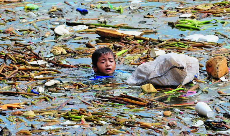 Dječak skuplja plastične boce duž obale Manilskog zaljeva