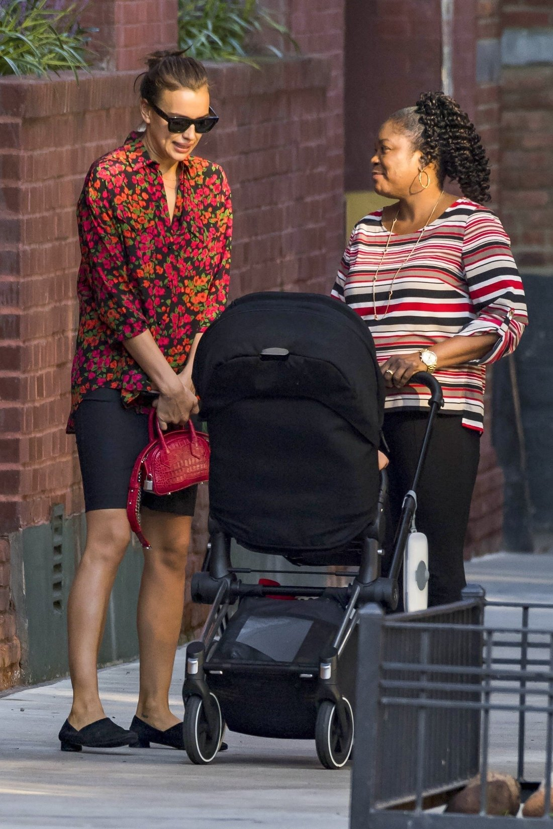 ** RIGHTS: WORLDWIDE EXCEPT IN BELGIUM, FRANCE, GERMANY, NETHERLANDS, POLAND ** New York, NY  - *EXCLUSIVE*  - Irina Shayk and her TWO nannies going for a stroll this morning in NY with a sleepy baby Lea de Seine. The famous supermodel wore a red graphic blouse matching her black skirt and comfy flats.  Pictured: Irina Shayk  BACKGRID USA 3 OCTOBER 2018, Image: 389645113, License: Rights-managed, Restrictions: , Model Release: no, Credit line: Profimedia, AKM-GSI