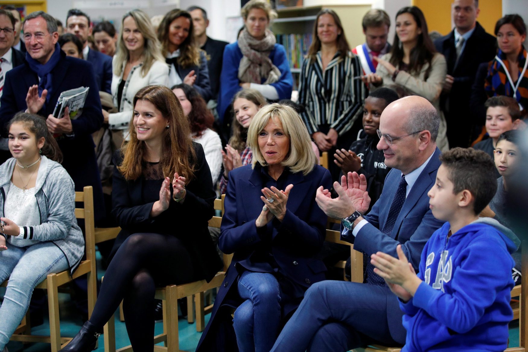 Brigitte Macron, wife of French President, French Education Minister Jean-Michel Blanquer and Marlene Schiappa, French Junior Minister for Gender Equality, applaud during a visit at a high school to discuss the fight against school bullying in Clamart, France, November 15, 2018.  REUTERS/Philippe Wojazer