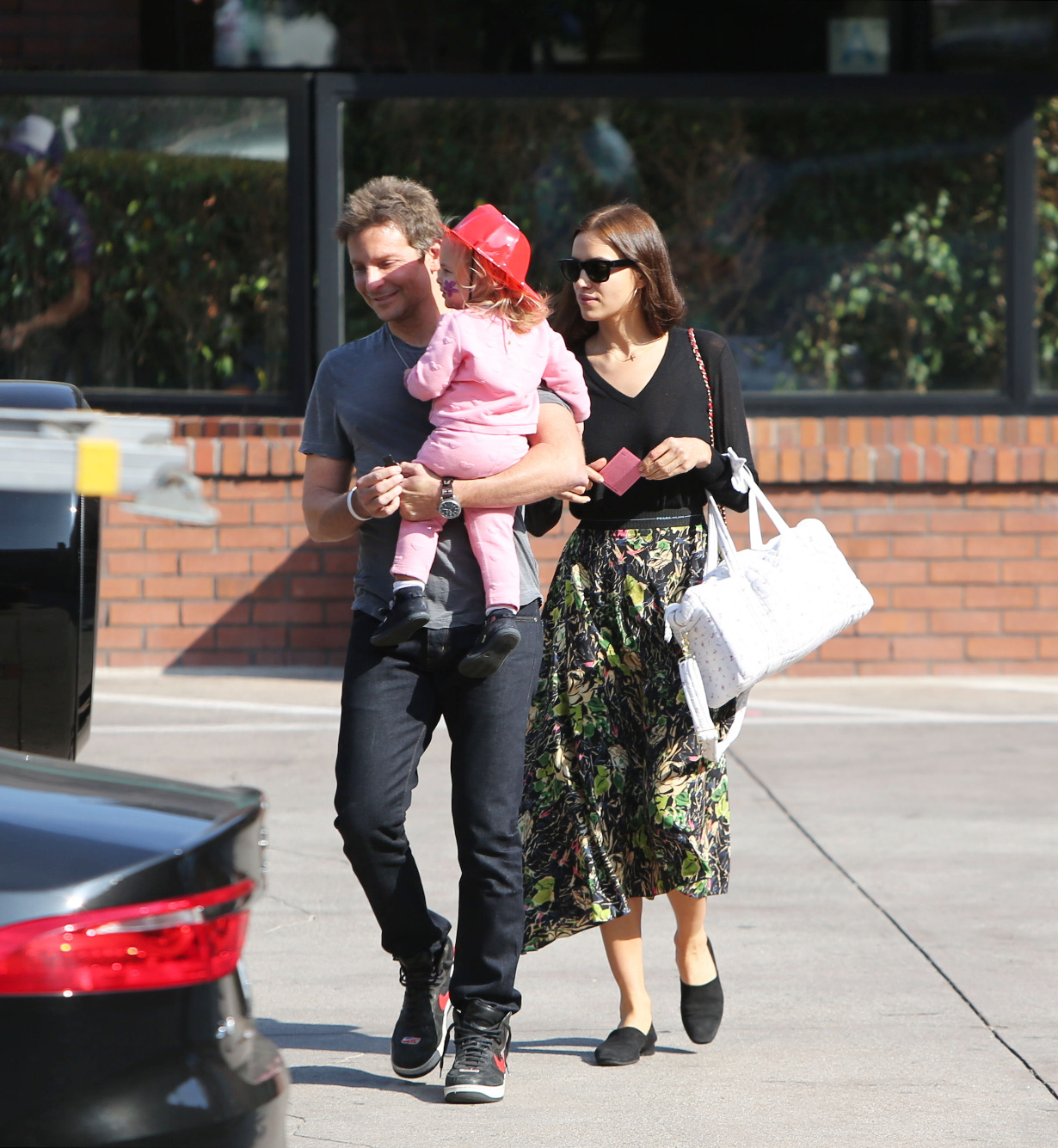 PREMIUM EXCLUSIVE Please contact X17 before any use of these exclusive photos - x17@x17agency.com   Wednesday, November 21, 2018 - Bradley Cooper and Irina Shayk gear up for a big day of eating tomorrow, taking daughter Lea along for some fun at the gym on the day before Thanksgiving. Their adorable one-year-old wears a fire chief helmet and a cute two-piece pink kitten ensemble while her supermodel mom is striking in a black v-neck blouse and floral skirt, paired with black flats.  Afterward, they stop by a medical center in their Mercedes G-Wagon. X17online.com
