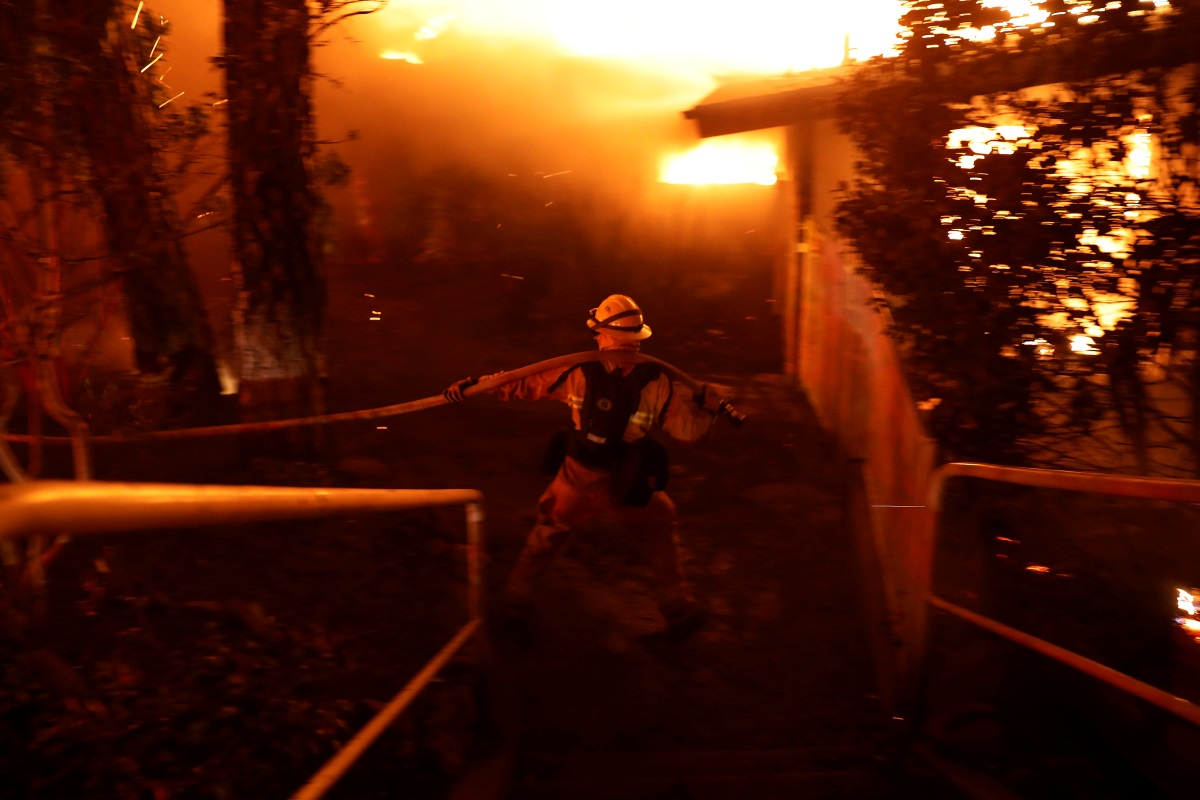A firefighter drags a hose as he battles the Camp Fire in Paradise, California, U.S. November 8, 2018. REUTERS/Stephen Lam