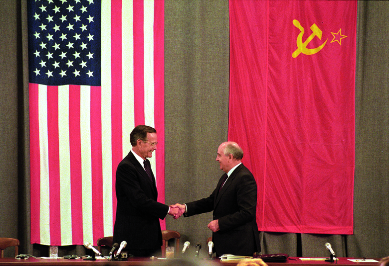 FILE PHOTO: U.S. President George H. W. Bush (L) and Soviet President Mikhail Gorbachev shake hands in front of U.S. and Soviet flags at the end of a news conference in Moscow July 31, 1991. REUTERS/Rick Wilking/File Photo