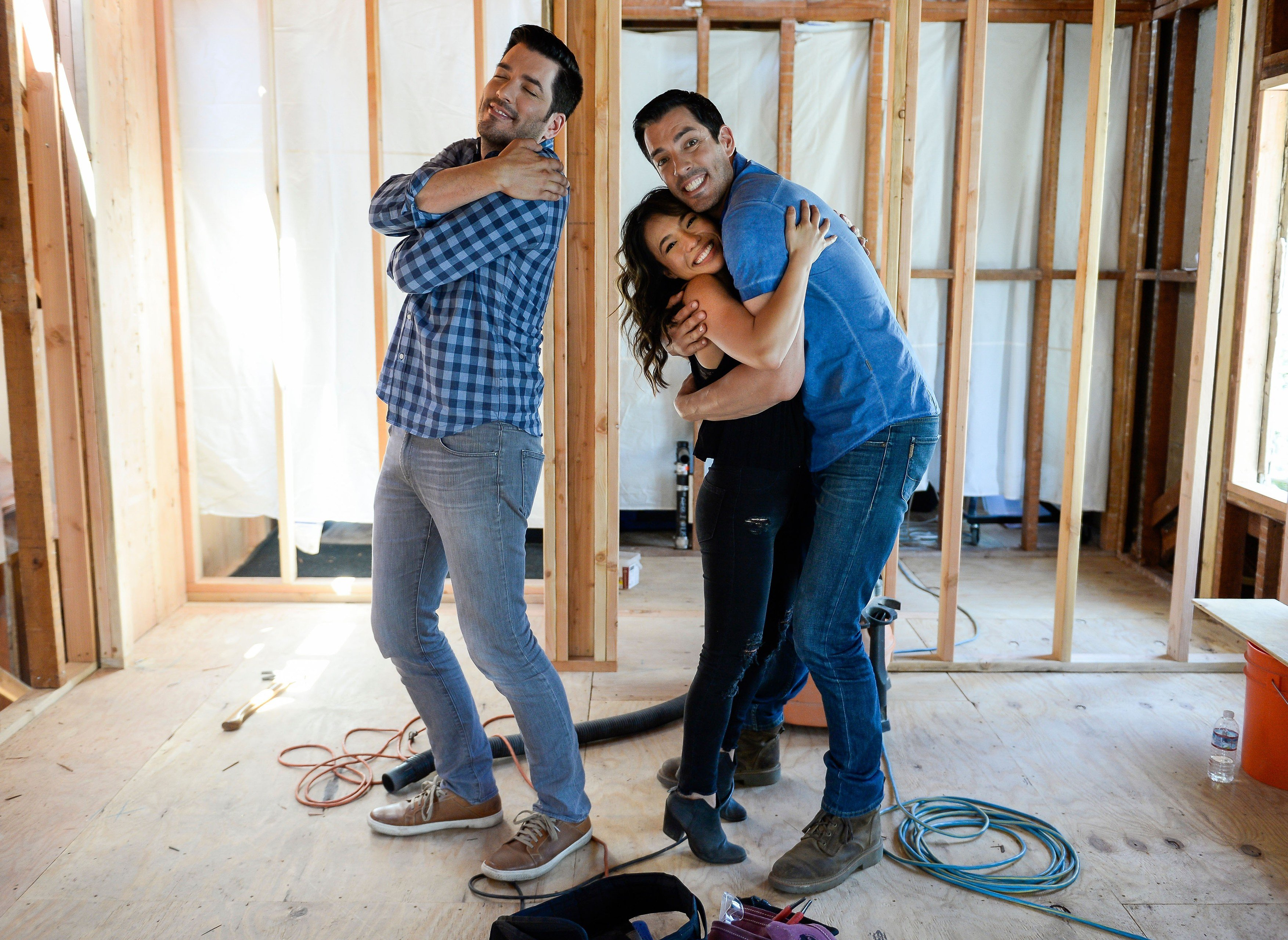 July 19, 2017; Los Angeles, CA, USA; Jonathan Scott (left) with his brother Drew Scott and Drew's fiancee Linda Phan (center) during the filming of \
