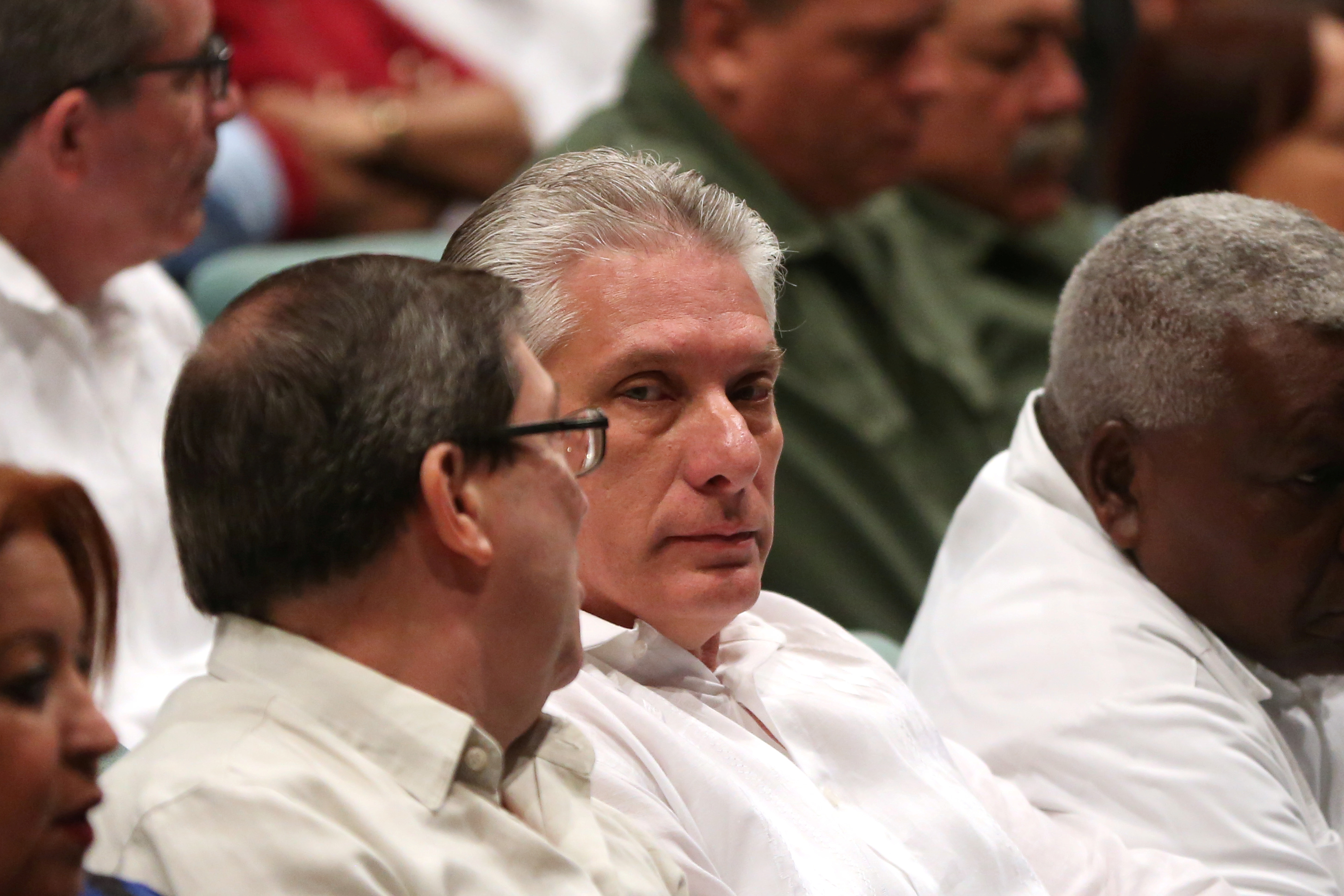 Cuba's First Vice-President Miguel Diaz-Canel (C) chats with Cuban Foreign Minister Bruno Rodriguez (back to camera) inside a theatre during the commemoration of the first anniversary of the interment of Castro's ashes in Santiago, Cuba, December 3, 2017. REUTERS/Alexandre Meneghini - RC14D1D35180