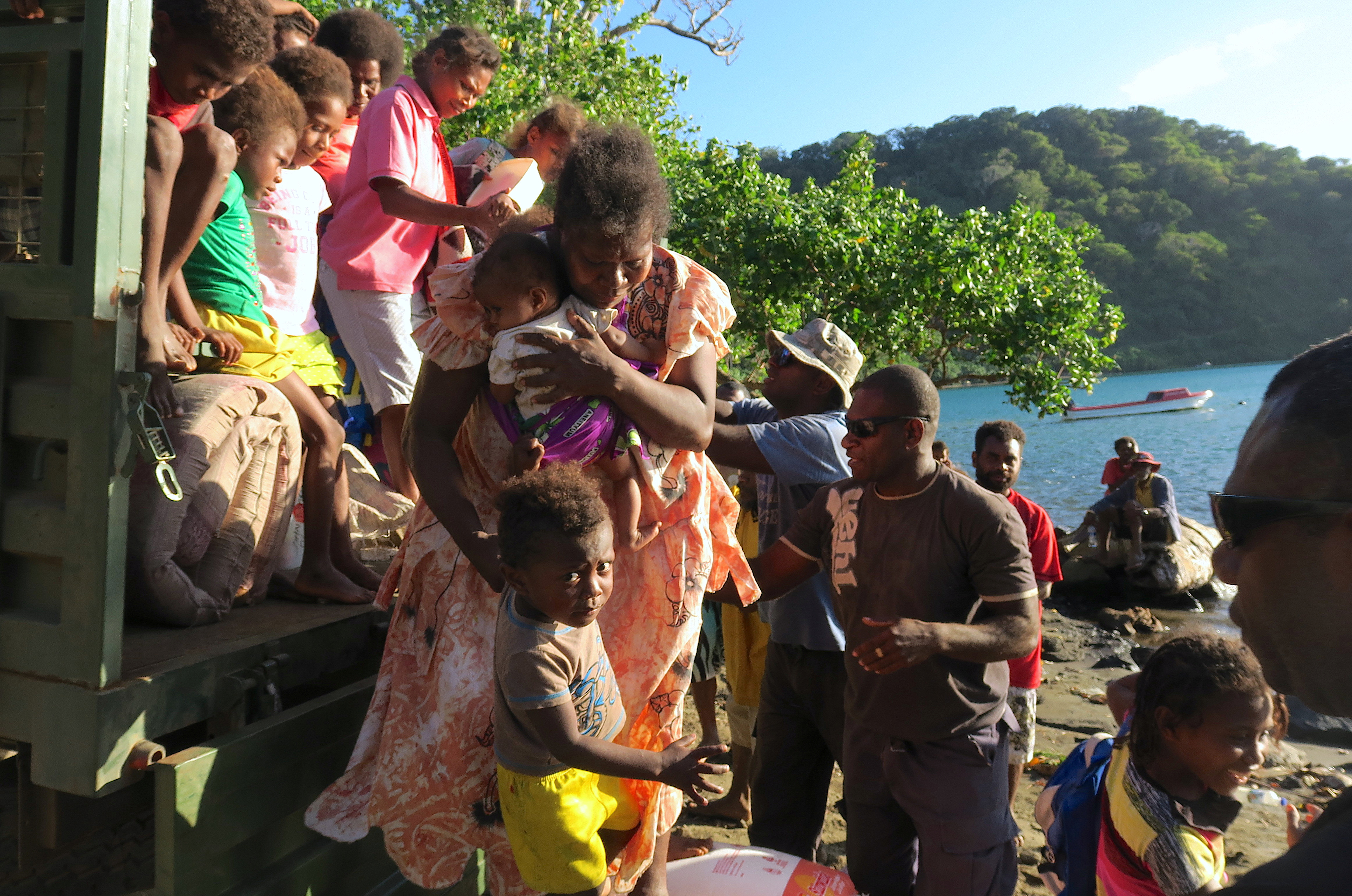 Residents carry their possessions as they prepare to board a boat at Lolowai Port as they evacuate due to the Manaro Voui volcano continuing to emenate smoke and ash on Vanuatu's northern island of Ambae in the South Pacific, October 1, 2017. Picture taken October 1, 2017.    REUTERS/Ben Bohane - RC1B9BEB6BC0