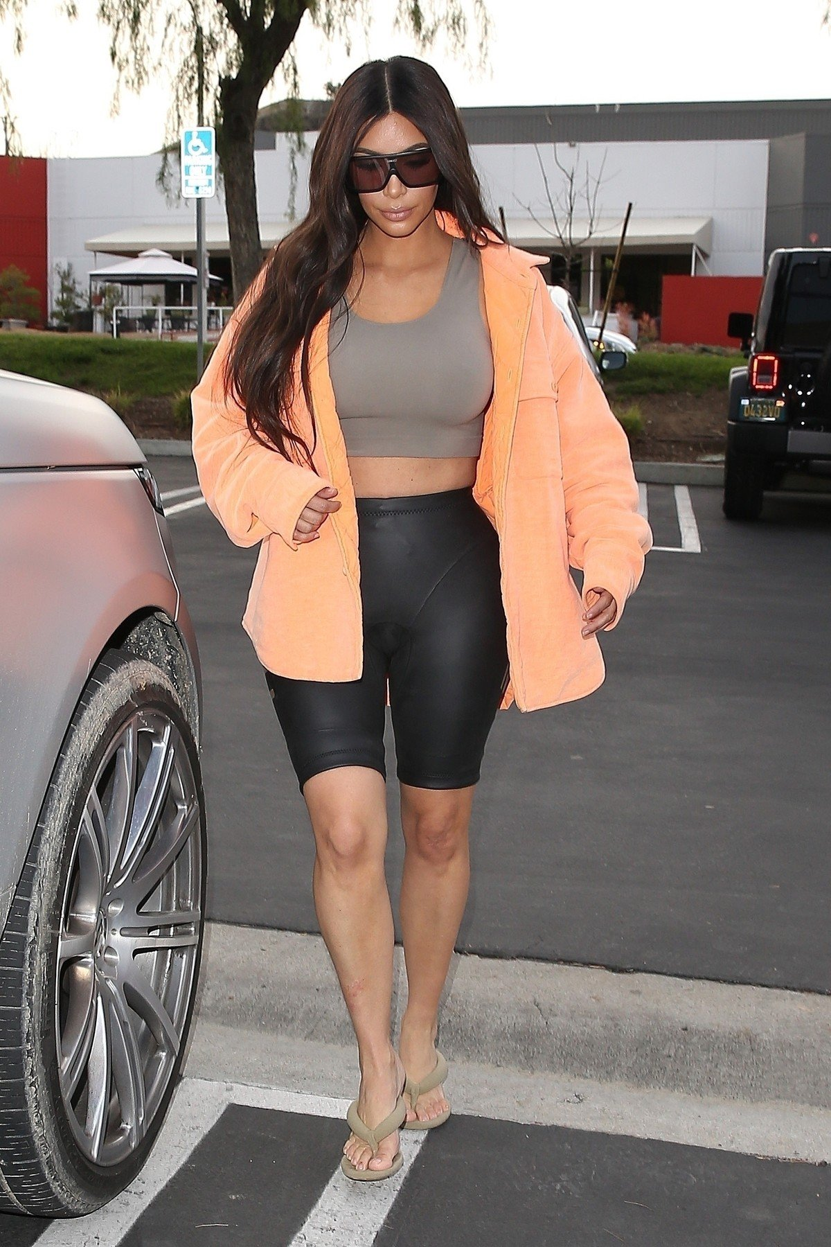 Calabasas, CA  - *EXCLUSIVE*  - Kanye West got an afternoon visit at the studio from his favorite muse, wife Kim Kardashian today. Kim paid a visit to her rapper/designer husband in black biker shorts,  bra top, peach coat and large sunnies after grocery shopping with sister Kourtney earlier in the day.  Kanye has a new shade of blonde and pink to his hair and wore a pair of all white Yeezy 350 V2 Triple White which are rumored to be re-releasing in the coming months.  Pictured: Kim Kardashian  BACKGRID USA 20 MARCH 2018, Image: 366451214, License: Rights-managed, Restrictions: , Model Release: no, Credit line: Profimedia, AKM-GSI