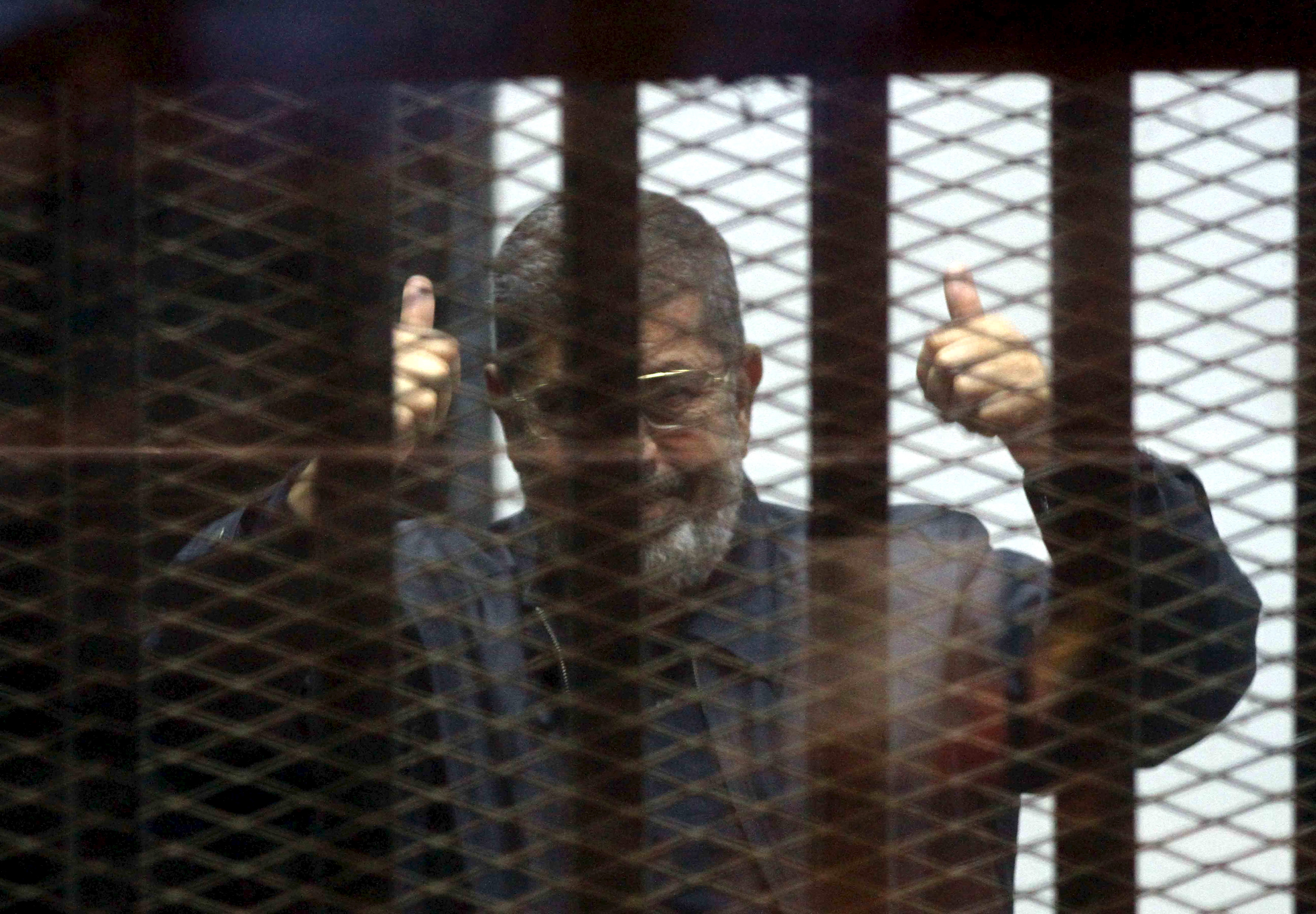 Ousted Egyptian President Mohamed Mursi is seen behind bars during his trial at a court in Cairo, April 30, 2015. REUTERS/Al Youm Al Saabi Newspaper. EGYPT OUT. NO COMMERCIAL OR EDITORIAL SALES IN EGYPT. TPX IMAGES OF THE DAY - GF10000078720