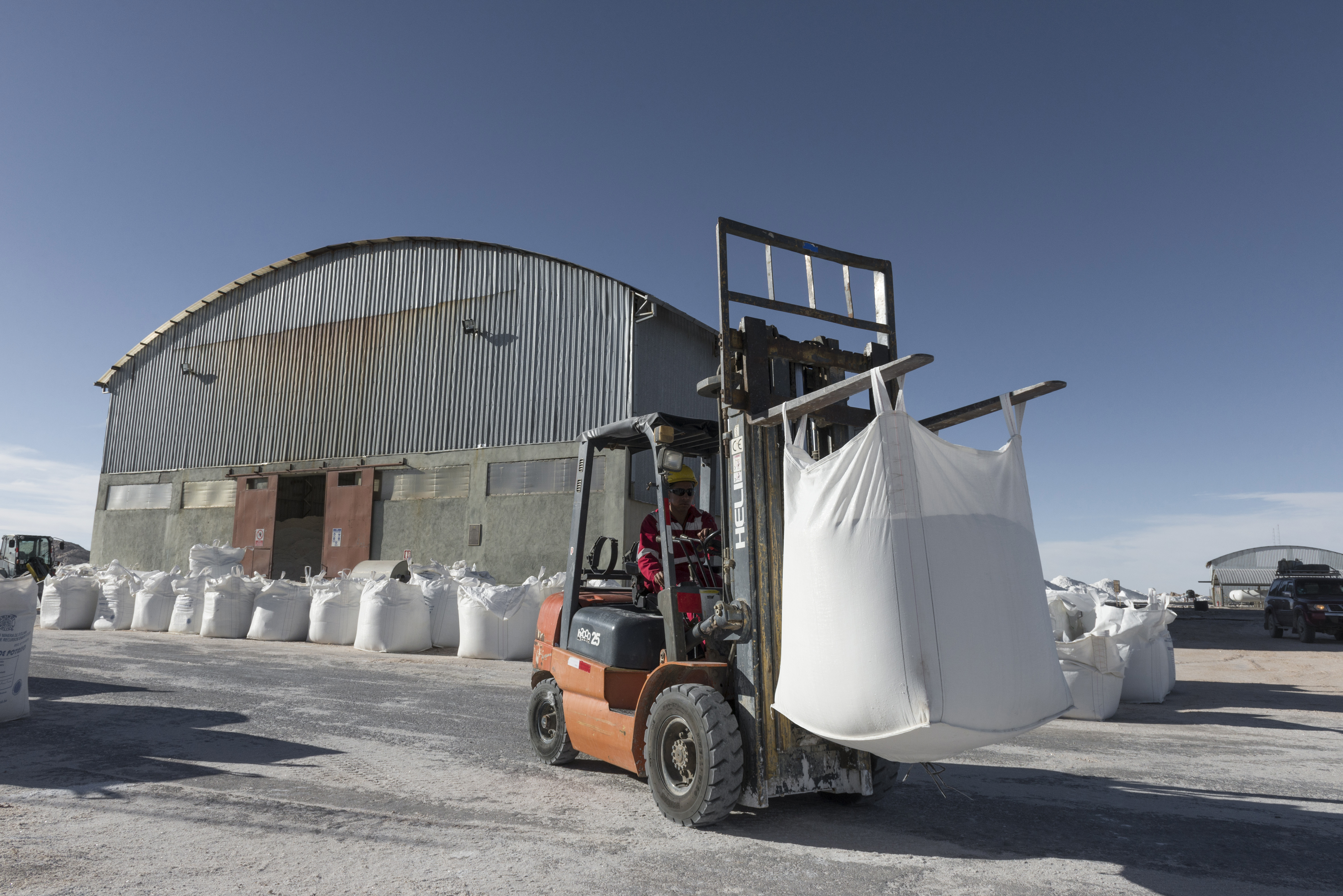 A worker moves bags of potassium chloride near the Potassium KCL Pilot facility inside the Salar de Uyuni (Salt Flats of Uyuni) in Potosi, Bolivia, on Saturday, Dec. 10, 2016. Bolivia has the largest lithium deposits of any country, which are estimated to be about half of the world's supply. Photographer: Marcelo Perez del Carpio/Bloomberg via Getty Images