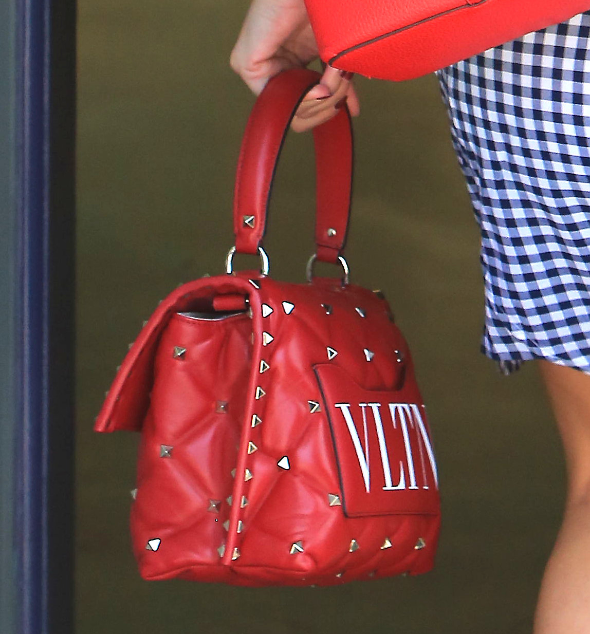 PREMIUM EXCLUSIVE Please contact X17 before any use of these exclusive photos - x17@x17agency.com   Wednesday, May 9, 2018 - Reese Witherspoon looks lovely in a gingham dress and red heels, carrying a red monogrammed Valentino Garavani VLTN Rockstud tote as she arrives at work in Brentwood, CA. The pricey tote sells for ,995 without customization, so it might've cost the A-list actress even more -- if it wasn't gifted by the designer! -  X17online.com