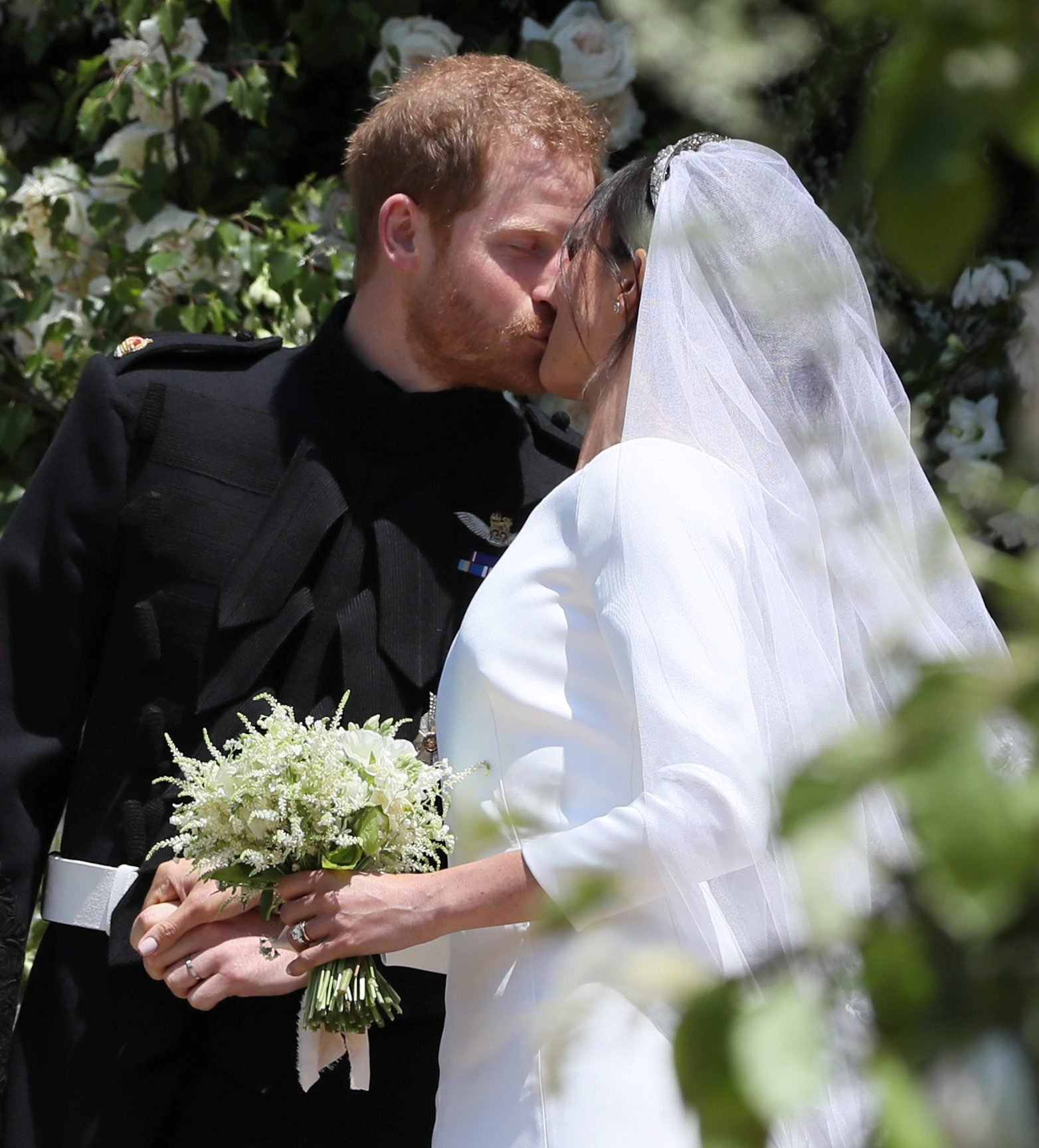 Prince Harry and Meghan Markle kiss as they leave St George's Chapel at Windsor Castle following their wedding in Windsor, Britain, May 19, 2018. Brian Lawless/Pool via REUTERS