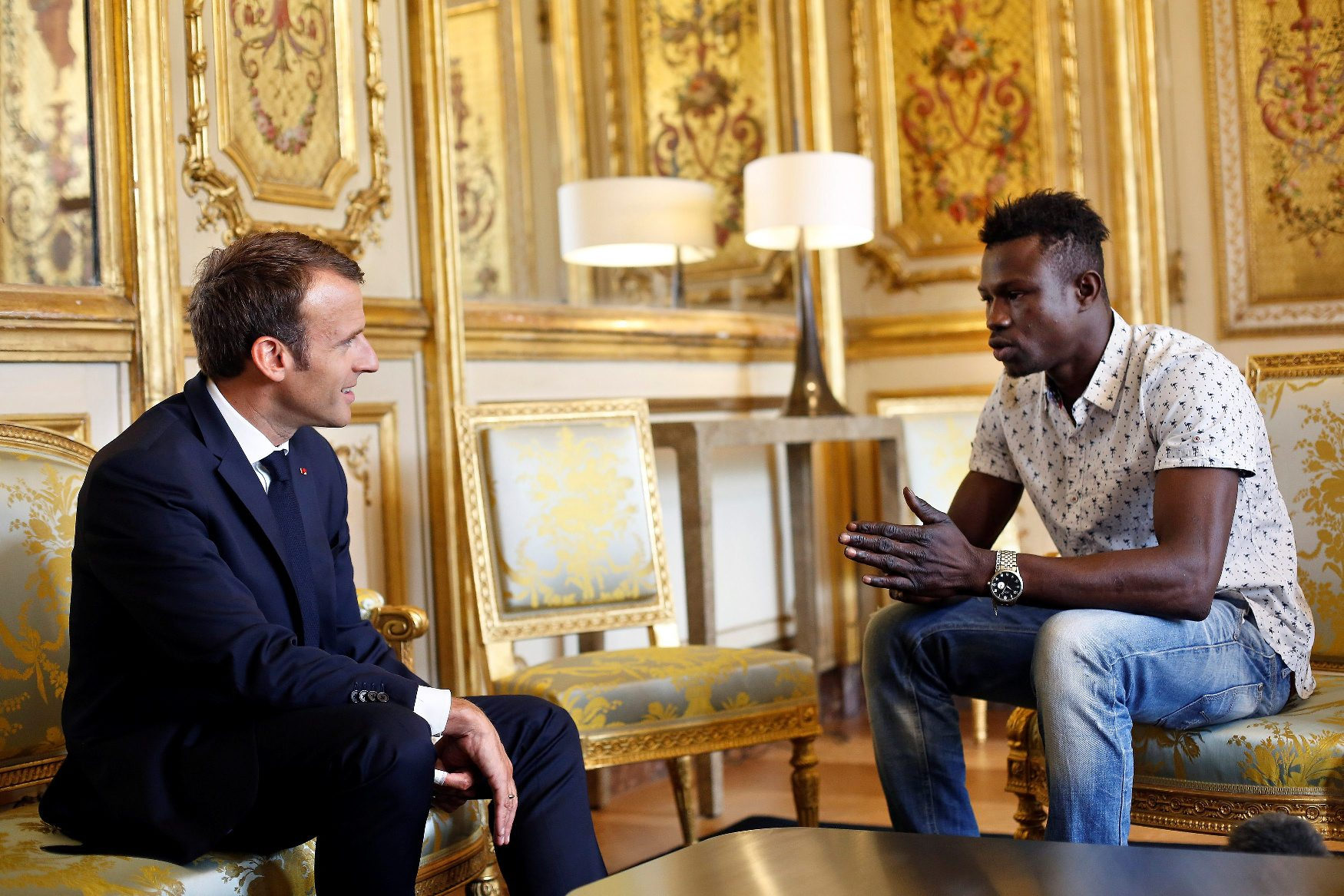 French President Emmanuel Macron (L) meets with Mamoudou Gassama, 22, from Mali, at the Elysee Palace in Paris, France, May 28, 2018. Mamoudou Gassama living illegally in France is being honored by Macron for scaling an apartment building over the weekend to save a 4-year-old child dangling from a fifth-floor balcony. Thibault Camus/Pool via Reuters