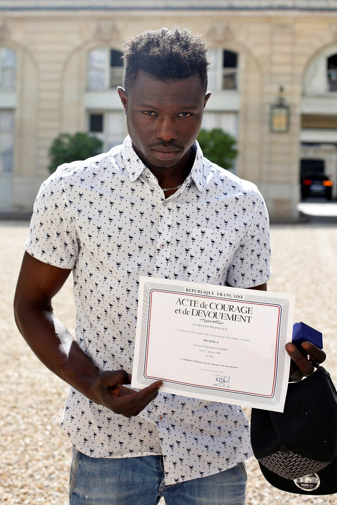 Mamoudou Gassama, 22, from Mali, displays a certificate of courage and dedication signed by Paris Police Prefect Michel Delpuech as he leaves the Elysee Palace after his meeting with French President Emmanuel Macron, in Paris, France, May 28, 2018. Mamoudou Gassama living illegally in France is being honored by Macron for scaling an apartment building over the weekend to save a 4-year-old child dangling from a fifth-floor balcony. Thibault Camus/Pool via Reuters