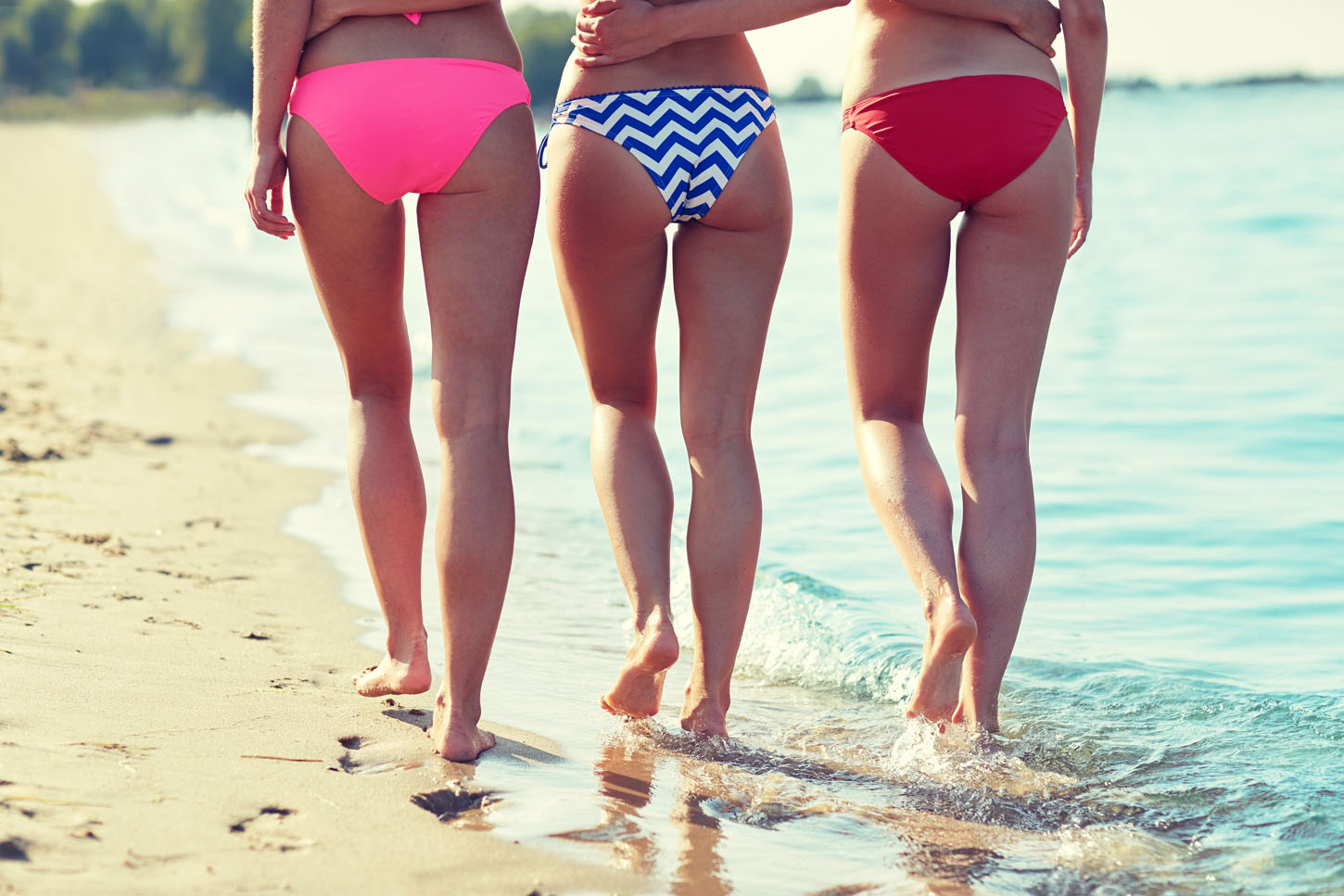summer holidays, travel, body care and people concept - close up of happy young women walking and hugging on beach from back