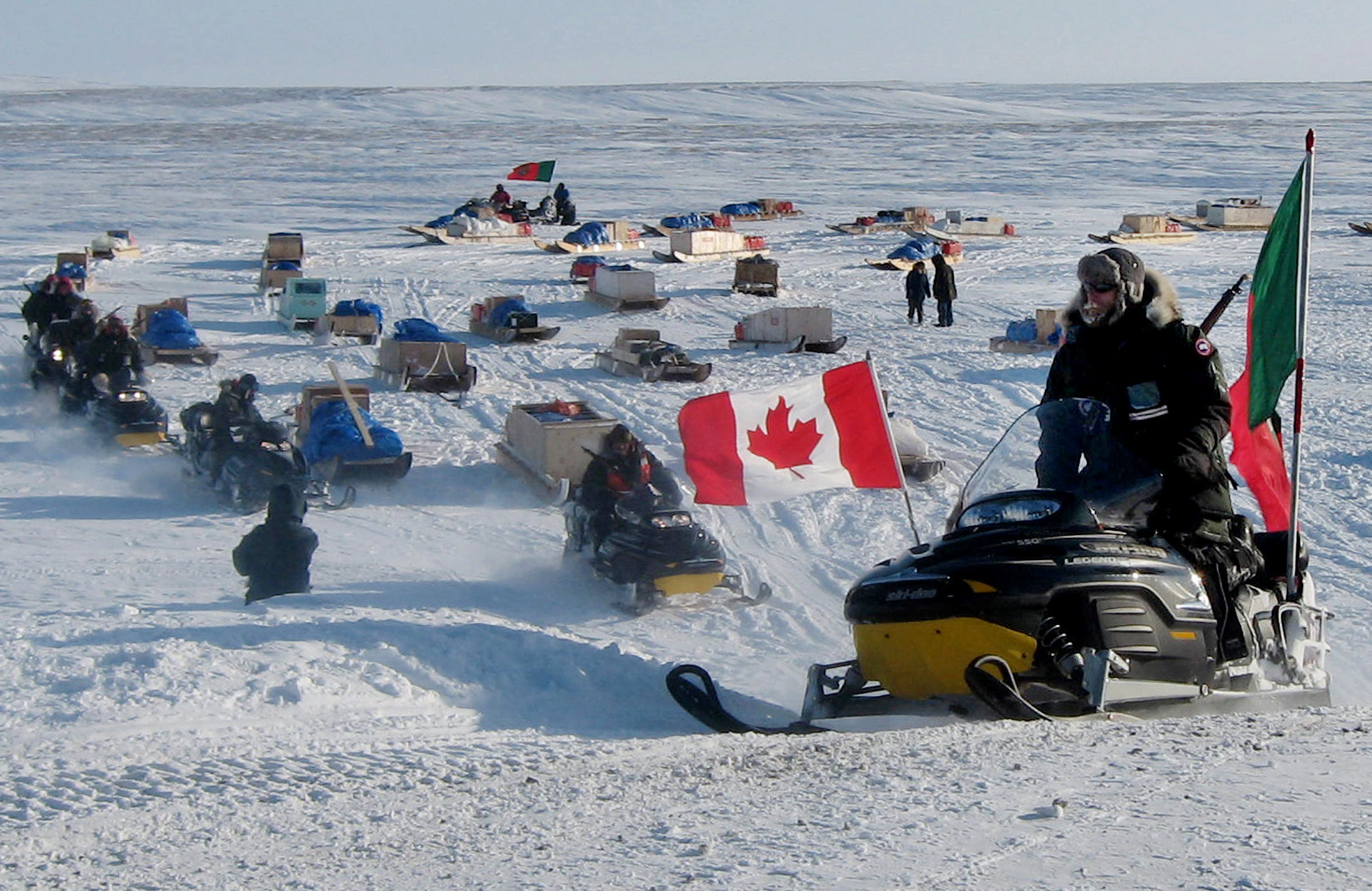 Canadian part-time military volunteers recruited from the aboriginal Inuit people ride their snowmobiles as they leave a meeting off Cornwallis Island, Nunavut April 9, 2006. They had gathered on the frozen sea off Cornwallis Island at the end of a two-week patrol designed to boost Canadian sovereignty in the remote and resource-rich High Arctic. After decades of virtually ignoring its remote, frozen Arctic lands, Canada is belatedly trying to assert its sovereignty over a gigantic region rich in mineral resources. The 1.3 million square miles (3.4 million sq km) of ice, rock and sea comprise 40 percent of Canada's land mass yet forces stationed there are minuscule -- 190 soldiers, 1700 part-time Inuit volunteers and four small, slow aircraft.  To match feature Canada-Sovereignty   Photo taken April 9, 2006.      REUTERS/David Ljunggren - GM1DSLAEZHAA
