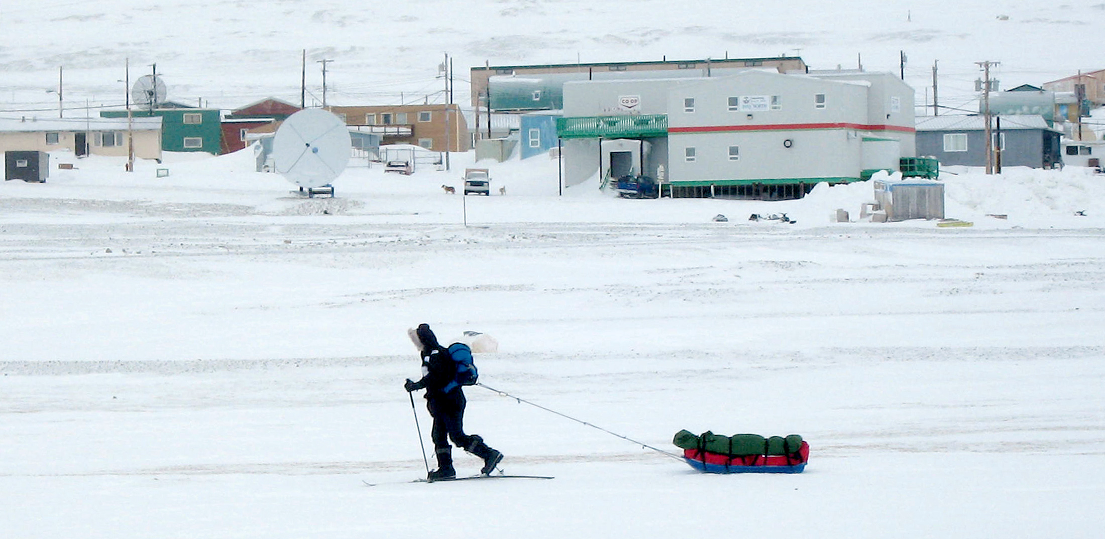 A man on skis travels across frozen sea past the Canadian Arctic settlement of Resolute Bay, Nunavut April 9, 2006. The settlement was founded in 1953 when the Canadian government dumped 14 aboriginal Inuit people on the frozen, stony beach. The Inuit say Ottawa tricked them into moving and some want an apology for the way they were treated. Picture taken April 9, 2006.   To match feature CANADA RELOCATION    REUTERS/David Ljunggren - GM1DSKUVBPAA