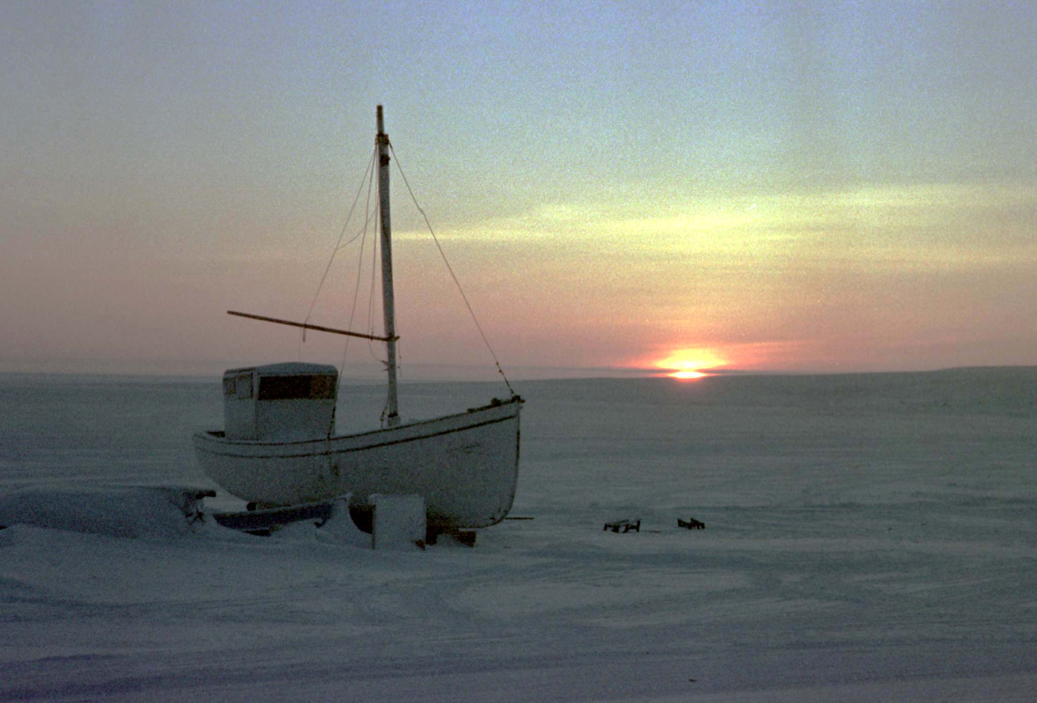 A small fishing boat sits on the shore of an Arctic island as the sun appears above the horizon for the first time following four months of polar darkness in one of Canada's northern most communities 1,921 Kms (1,200 miles) from the North Pole, January 18, 1999. The sun only appears on the horizon for about 10 or 20 minutes before setting again. The appearance of the sun has deep significance in Inuit life and signals the begining of new hunting season. REUTERS/Christopher Wilson   (CANADA) - WASE53P1AUC01