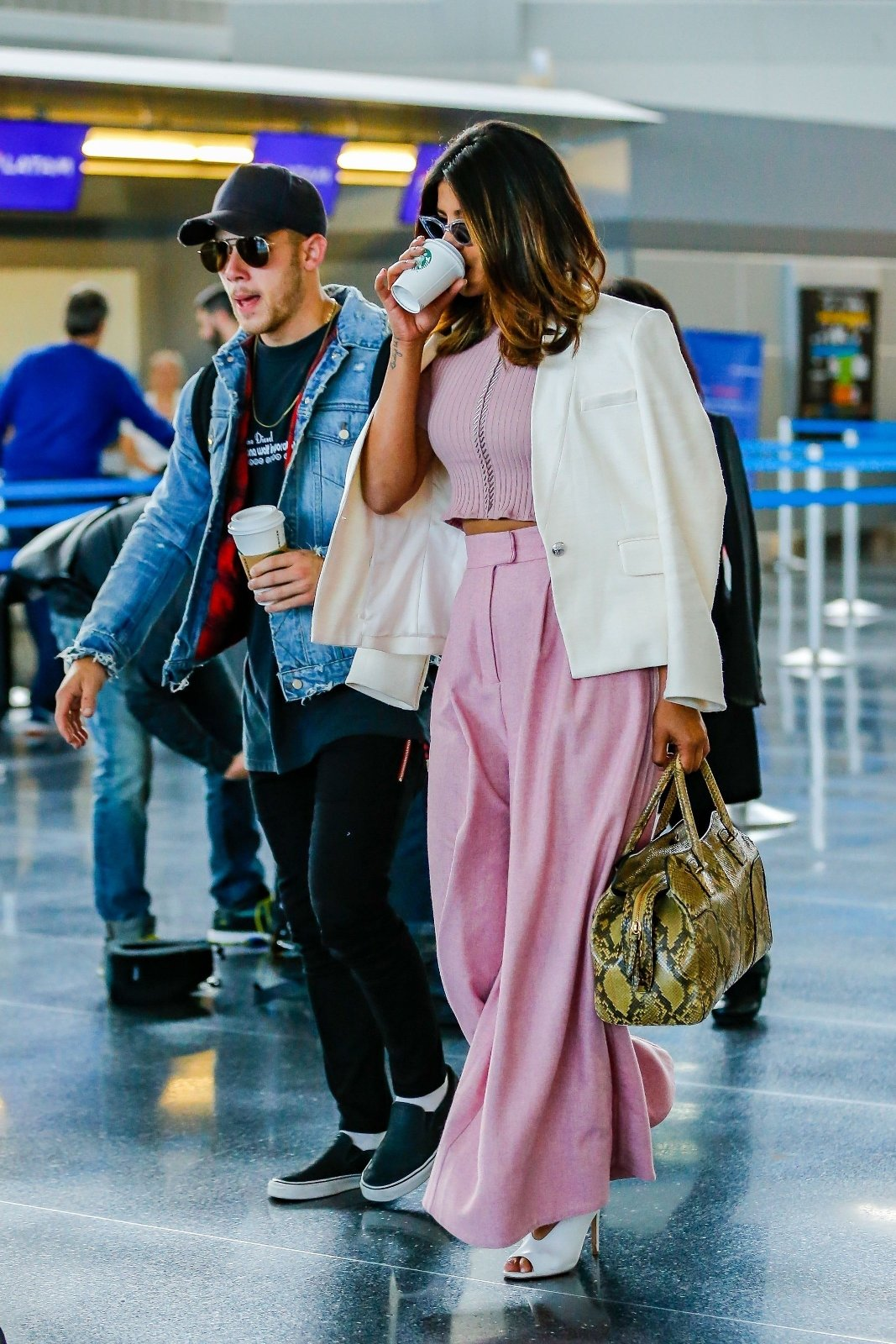 New York City, NY  - Actress Priyanka Chopra shows off her style in a beautiful pink and white ensemble while singer Nick Jonas goes for the casual look while touching down at JFK Airport in New York City. The hot new couple were both enjoying some coffee during their arrival.  Pictured: Nick Jonas, Priyanka Chopra    *UK Clients - Pictures Containing Children Please Pixelate Face Prior To Publication*, Image: 374265029, License: Rights-managed, Restrictions: , Model Release: no, Credit line: Profimedia, AKM-GSI