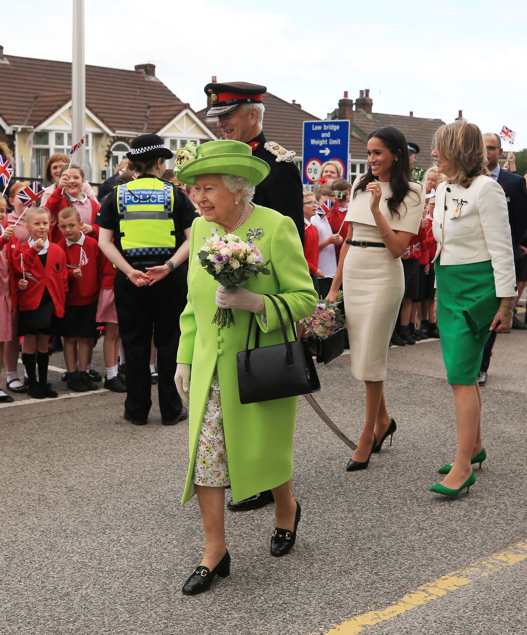 RUNCORN, CHESHIRE, ENGLAND - JUNE 14:  Queen Elizabeth II holds flowers as she and Meghan, Duchess of Sussex greet the crowds after arriving by Royal Train at Runcorn Station to open the new Mersey Gateway Bridge on June 14, 2018 in the town of Runcorn, Cheshire, England. Meghan Markle married Prince Harry last month to become The Duchess of Sussex and this is her first engagement with the Queen. During the visit the pair will open a road bridge in Widnes and visit The Storyhouse and Town Hall in Chester.  (Photo by Peter Byrne - WPA Pool/Getty Images)