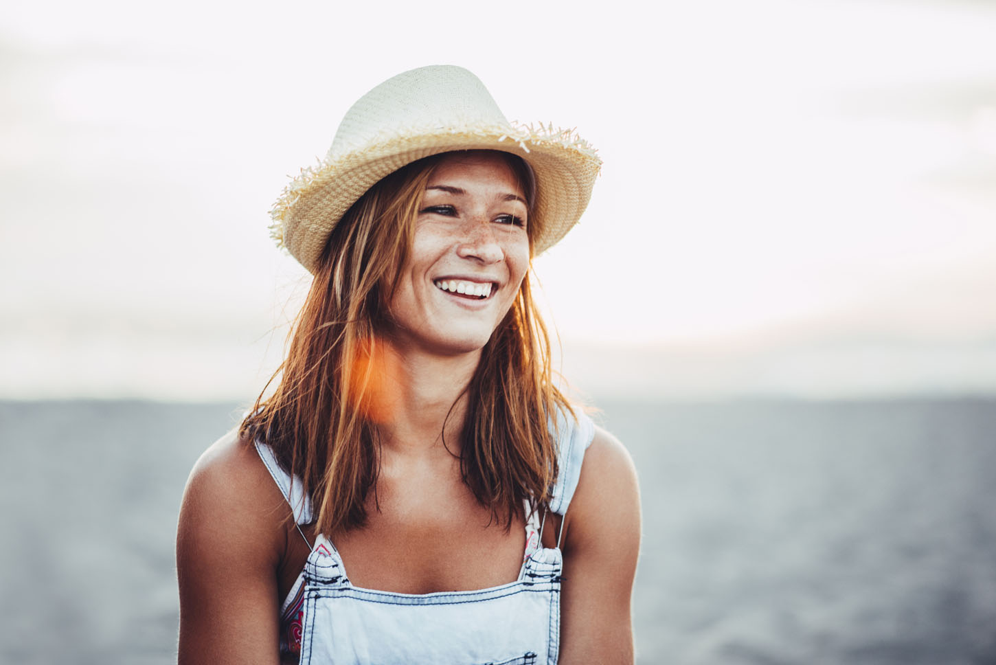 Girl with the hat smiling to the sun.